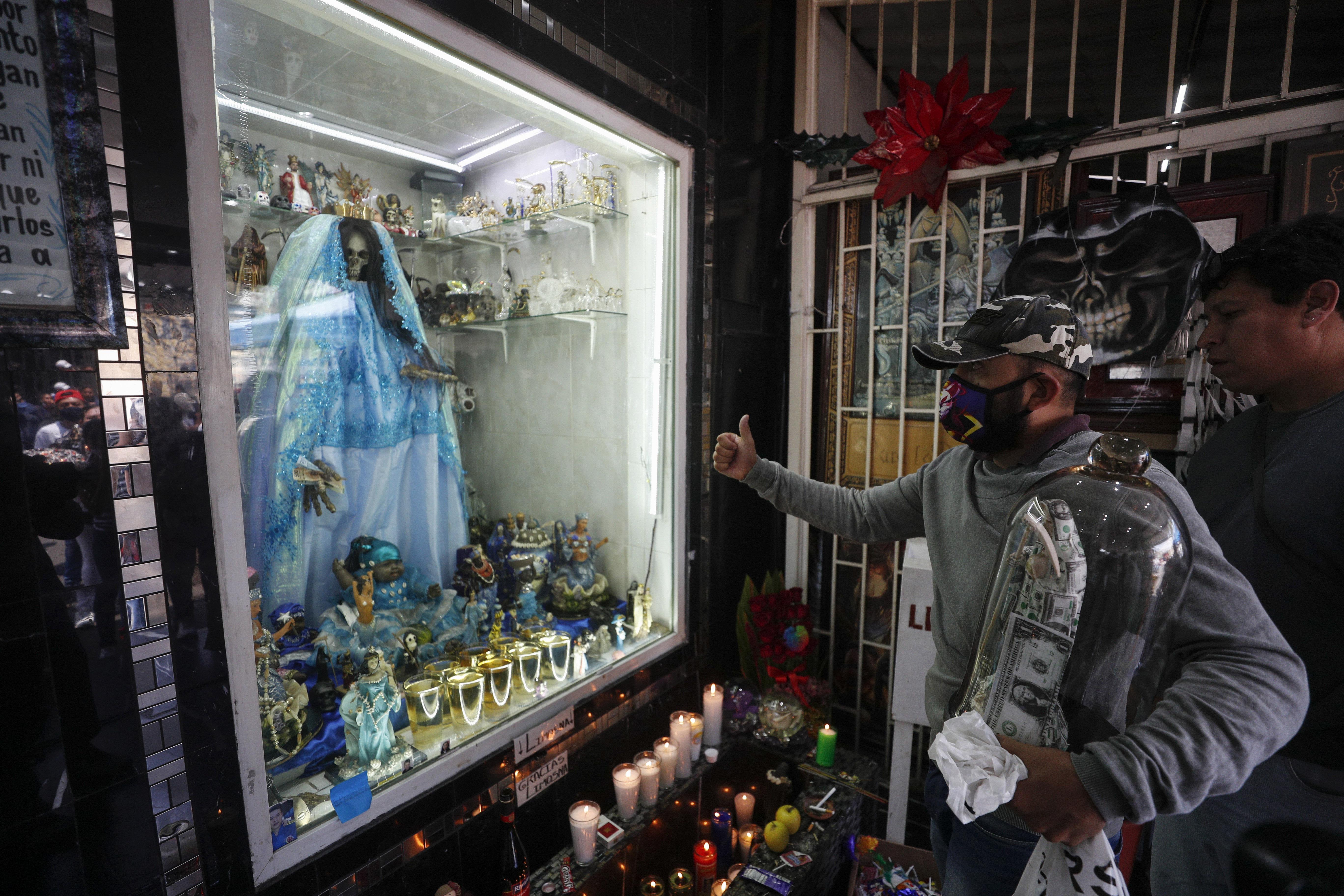 Un devoto de Santa Muerte da un pulgar hacia arriba mientras le presenta sus respetos en un altar en el barrio de Tepito. (Foto: AP / Rebecca Blackwell)