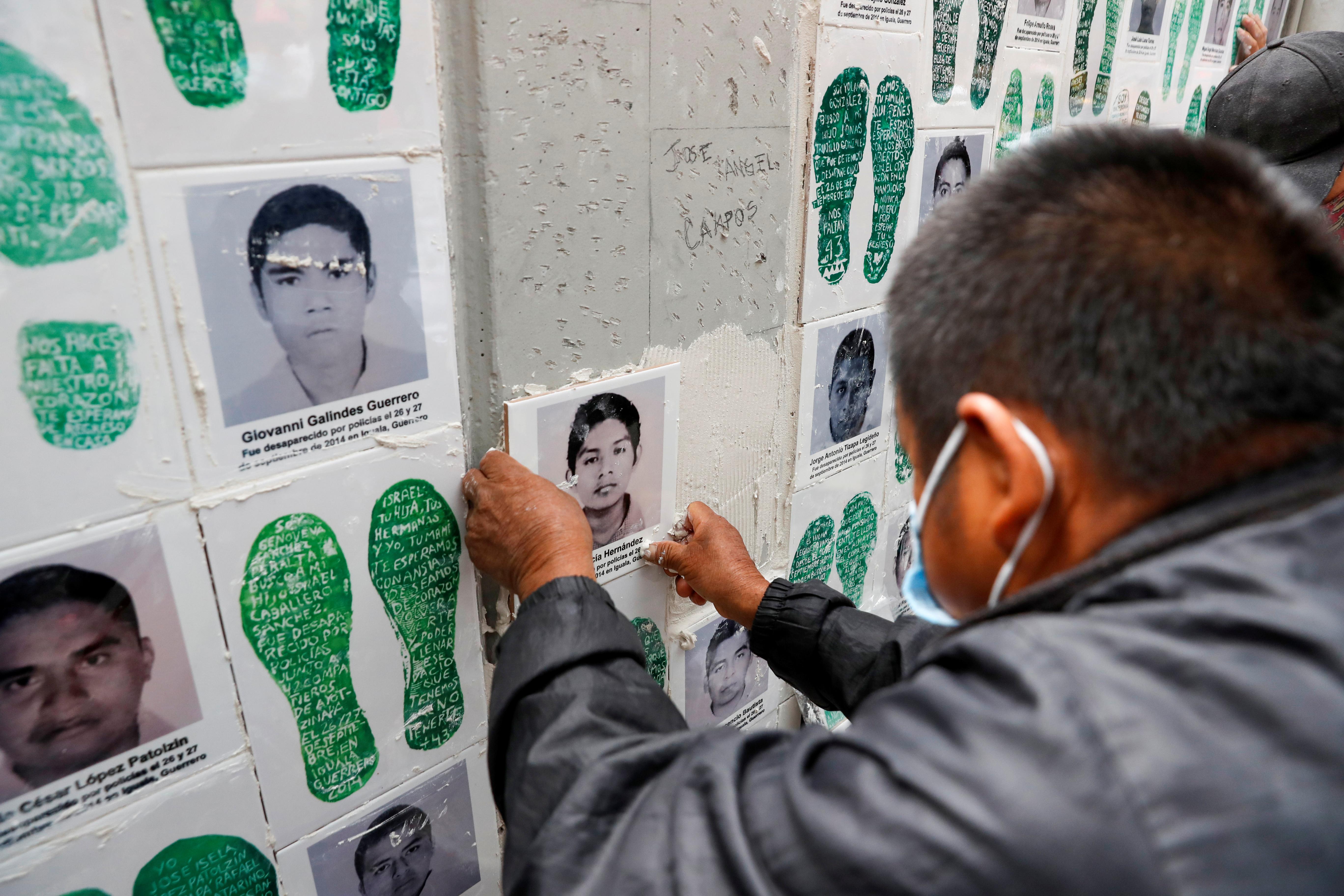 Un familiar de un estudiante desaparecido coloca una cerámica con su imagen en una pared durante una protesta frente a la Fiscalía General, antes del sexto aniversario de la desaparición de 43 estudiantes de la Escuela Normal Rural de Ayotzinapa, en la Ciudad de México, México el 25 de septiembre de 2020.