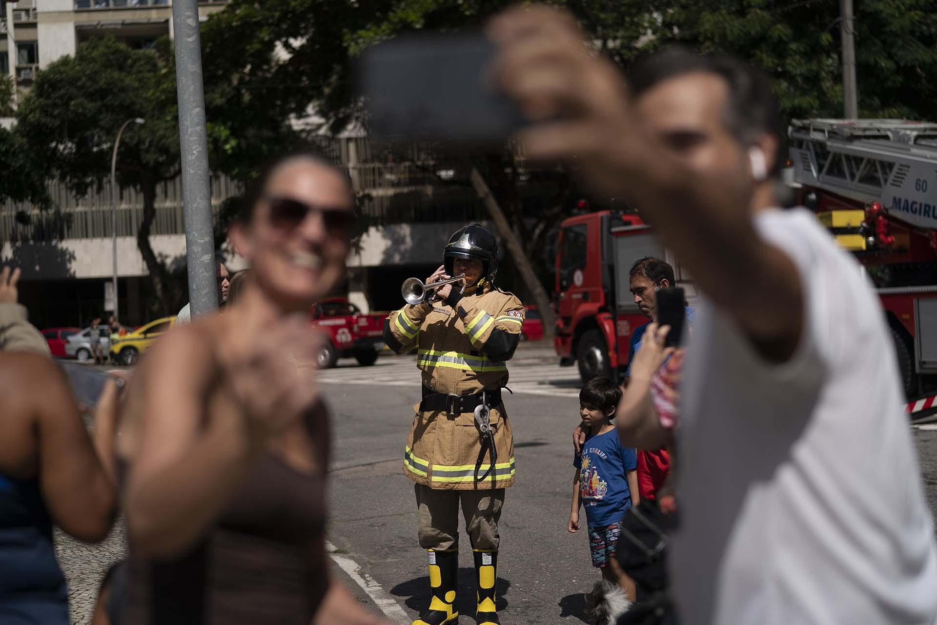 Reisdentes se toman una fotografía con el bombero Elielson Silva mientras éste toca la trompeta, en Río de Janeiro, Brasil (AP Photo/Leo Correa)