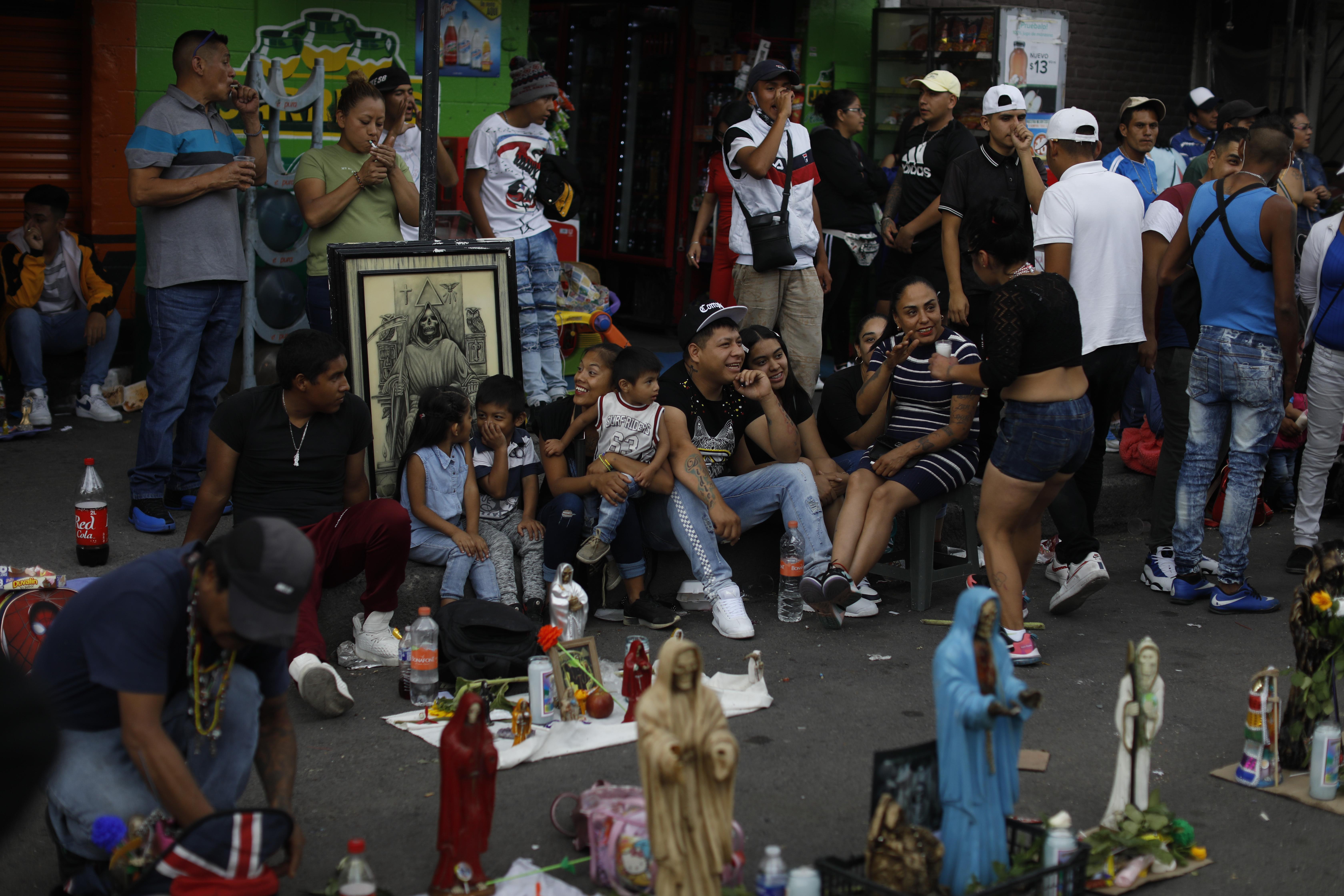 Los devotos de la Santa Muerte se amontonan en la calle mientras celebran su día festivo mensual frente a un altar en el barrio de Tepito, Ciudad de México, el lunes 1 de junio de 2020. (Foto: AP / Rebecca Blackwell)