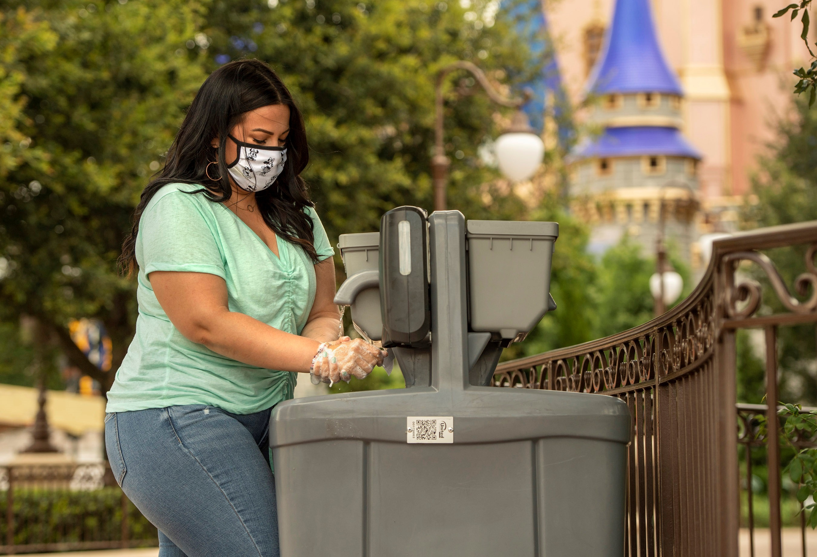 Una mujer con tapaboca se lava las manos en el interior de uno de los parques