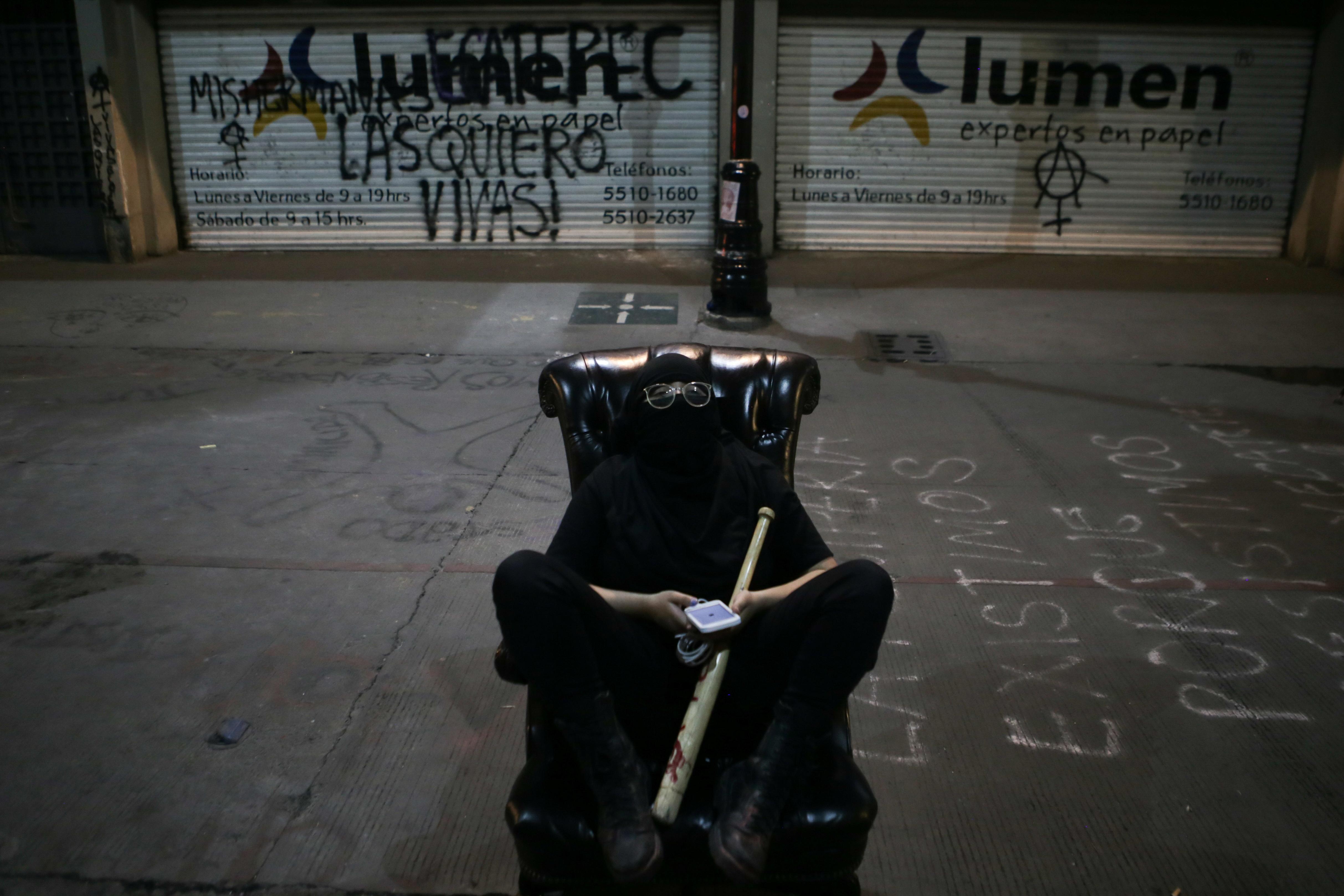 Una integrante de un colectivo feminista sentada en la silla de una Comisión Nacional de Derechos Humanos mientras monta guardia en la calle durante la noche fuera de las instalaciones del edificio de la Comisión Nacional de Derechos Humanos, en apoyo a las víctimas de violencia de género, en la Ciudad de México, México 11 de septiembre , 2020. Foto tomada el 11 de septiembre de 2020.