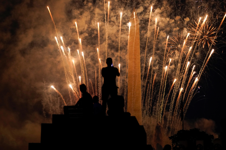 Un grupo de personas tratan fotografiar los fuegos artificiales