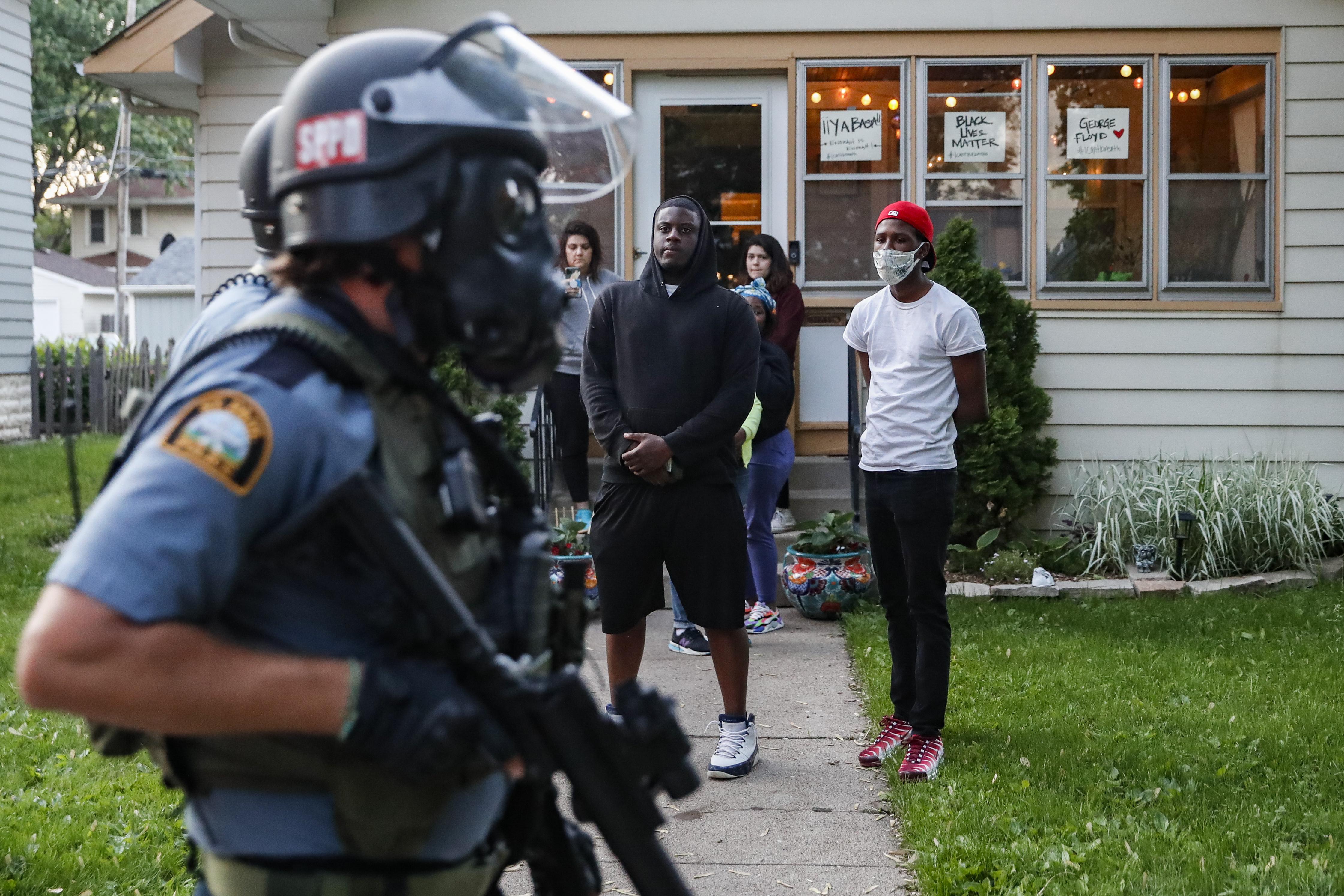 Un grupo de personas observa a la policía con equipo antidisturbios caminando por una calle residencial en St. Paul, Minnesota (AP Photo/John Minchillo)