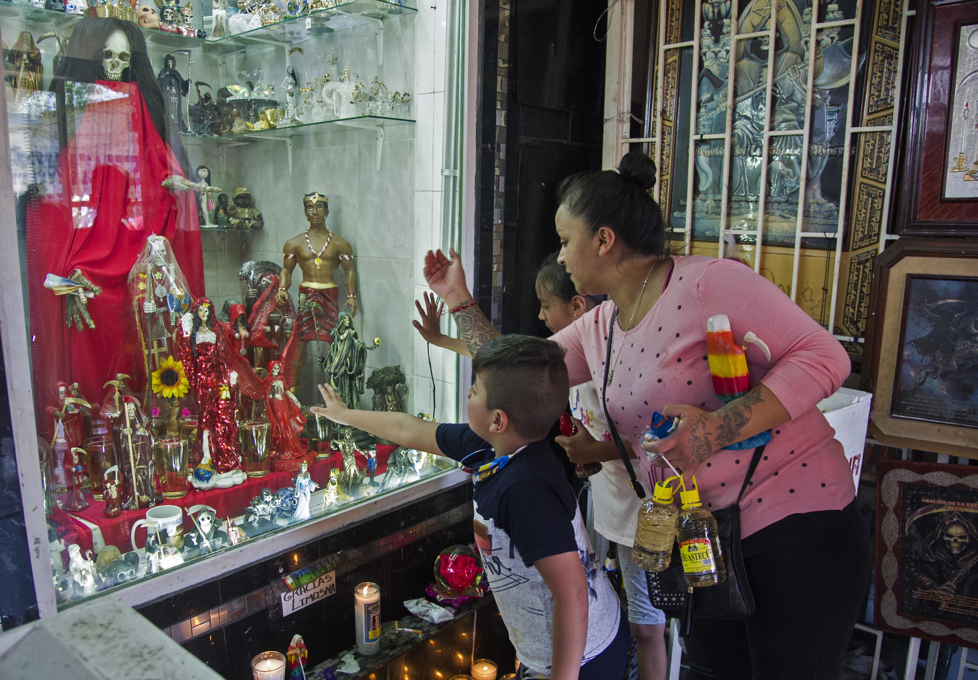 Una mujer y sus hijos tocan el cristal del santuario de Santa Muerte en la calle Alfarería, en el barrio de Tepito, de la Ciudad de México, el 1 de octubre de 2020