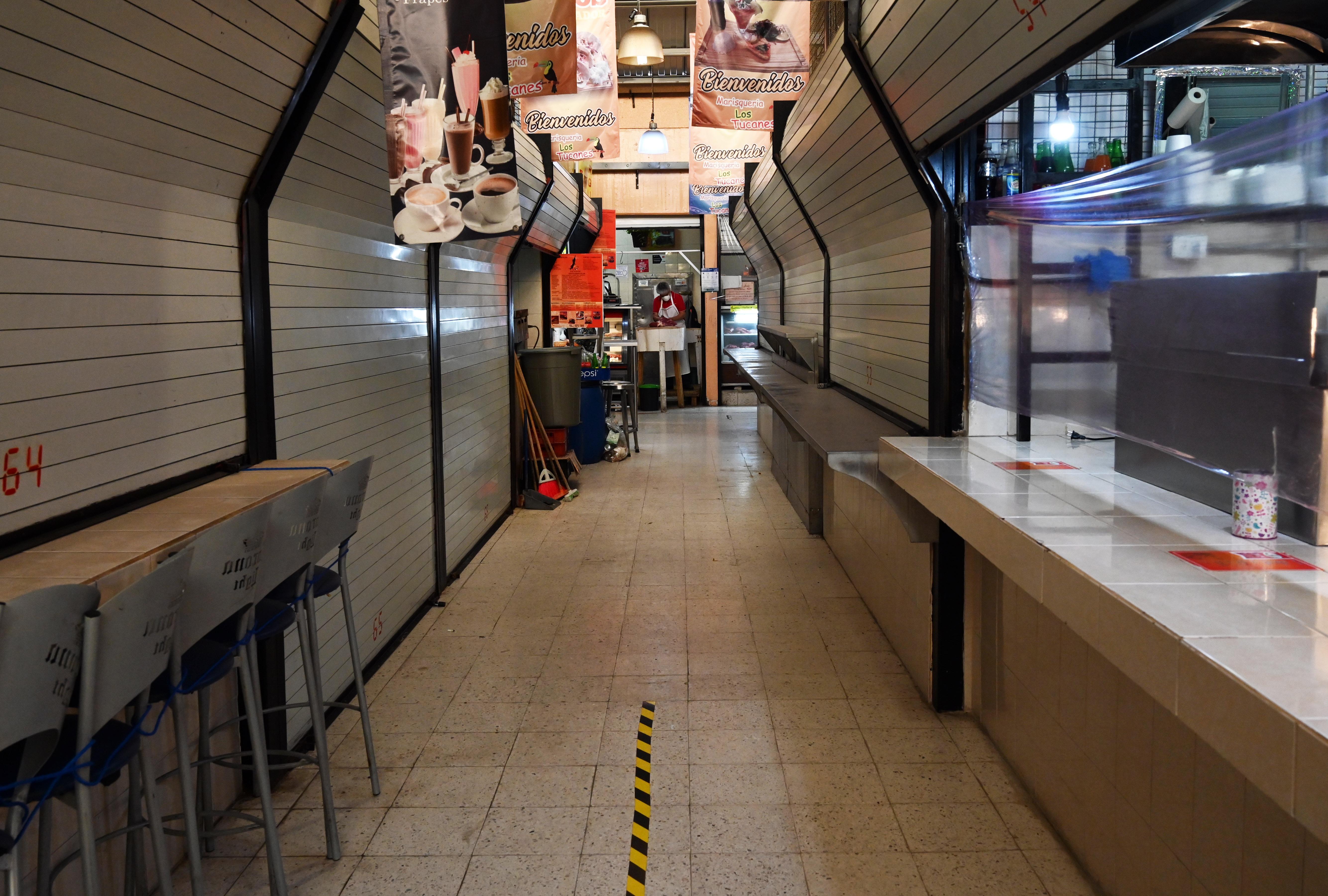 Un hombre trabaja en su carnicería, mientras que los restaurantes permanecen cerrados en un mercado popular en la Ciudad de México el 29 de junio de 2020. (Foto: RODRIGO ARANGUA / AFP)