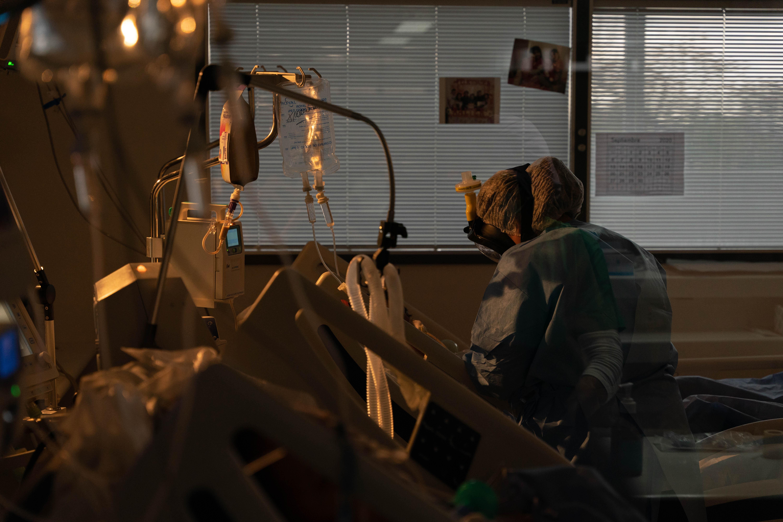 Una enfermera trabaja sobre un paciente con su máscara de snorkel adaptada. Las donó una ONG y son más cómodas para trabajar que el barbijo tradicional.