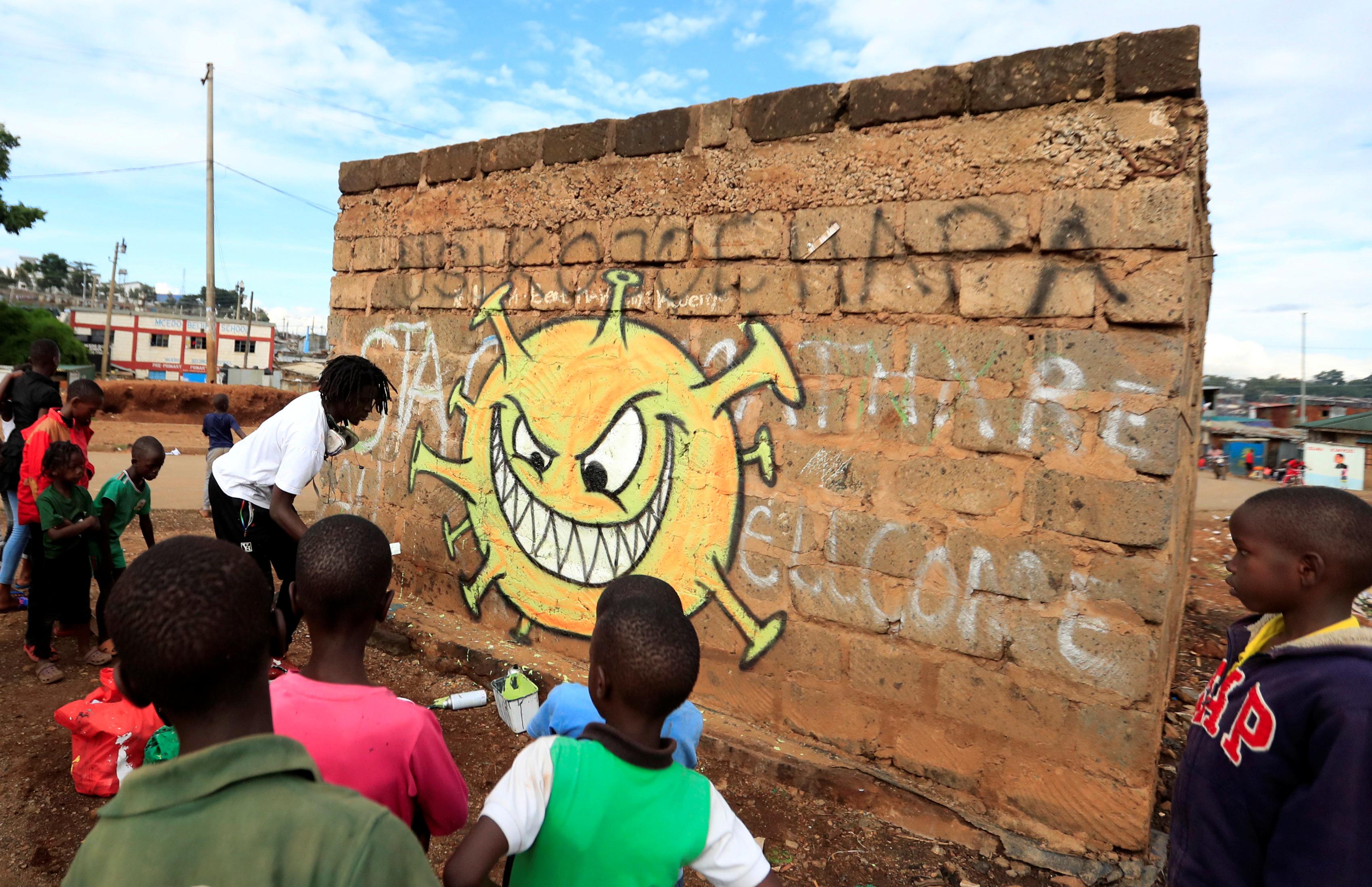 Niños observan a Brian Musasia Wanyande terminando su graffiti en el barrio popular del Valle de Mathare en Nairobi, Kenia