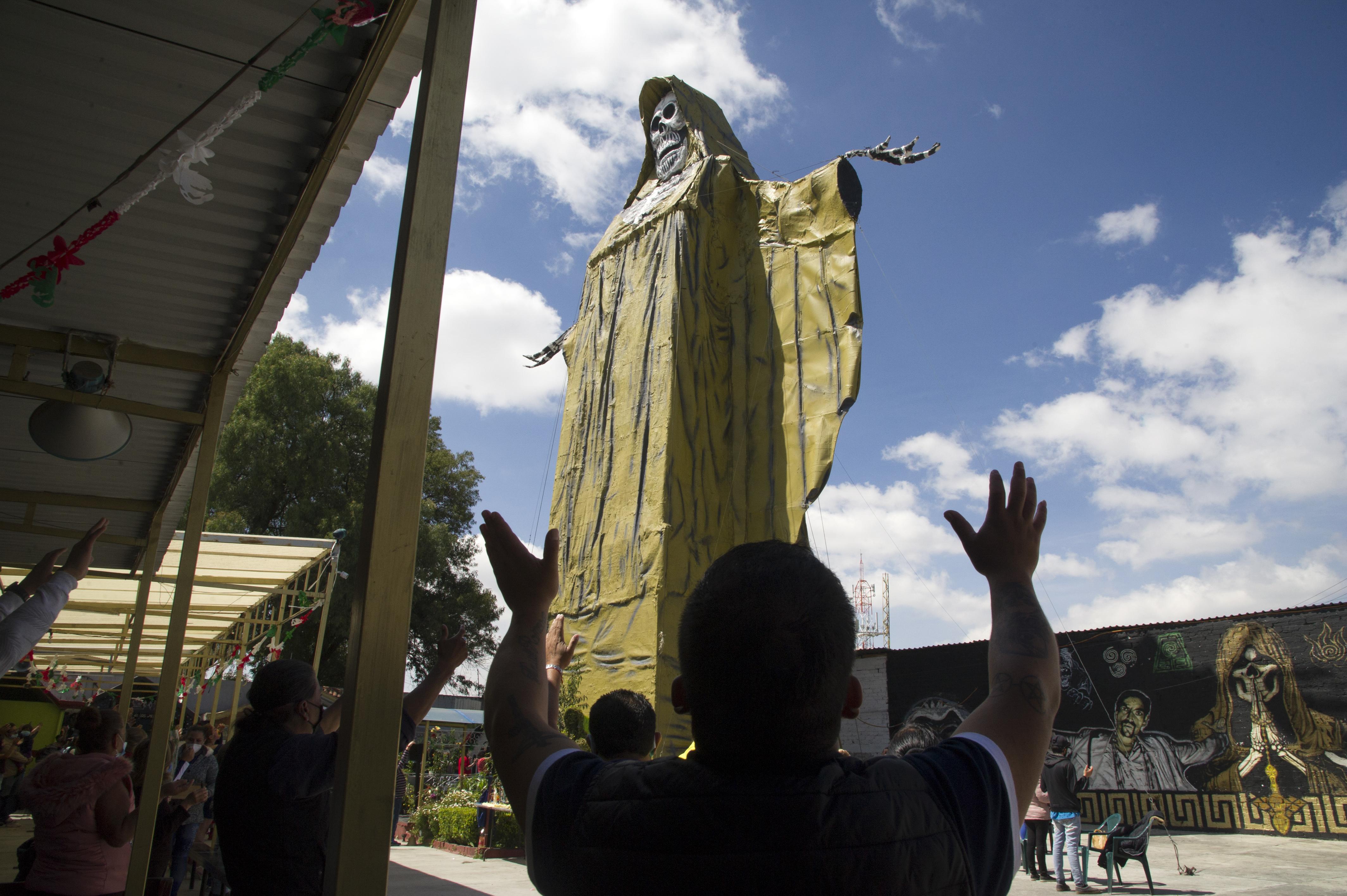 Los devotos levantan los brazos junto a la Santa Muerte de 22 metros de altura durante una ceremonia en el Santuario Internacional de la Santa Muerte en el municipio de Tultitlán, Estado de México, México, el 4 de octubre de 2020