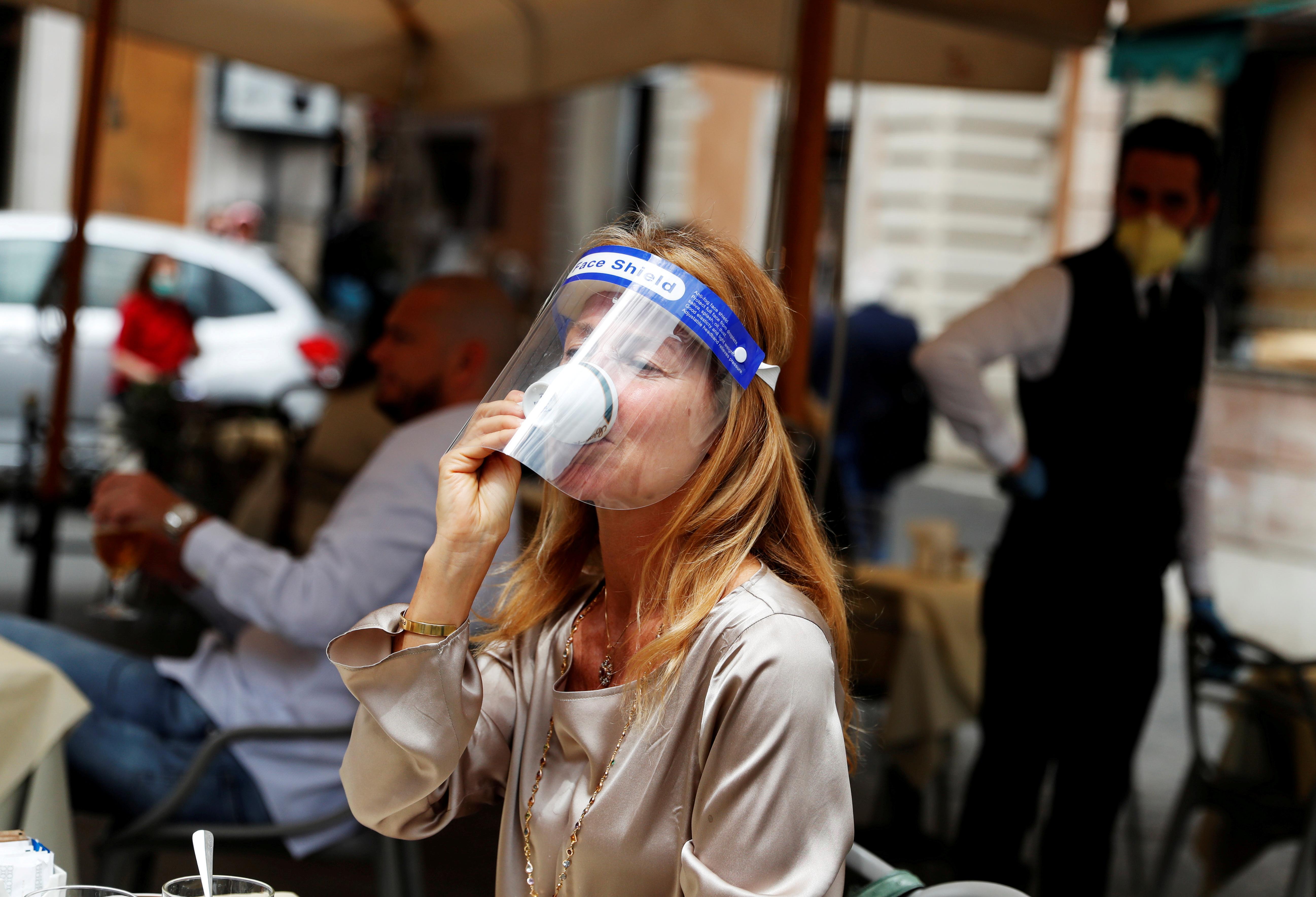Una mujer con una máscara protectora toma un café en un bar de Roma este lunes (Reuters/ Yara Nardi)