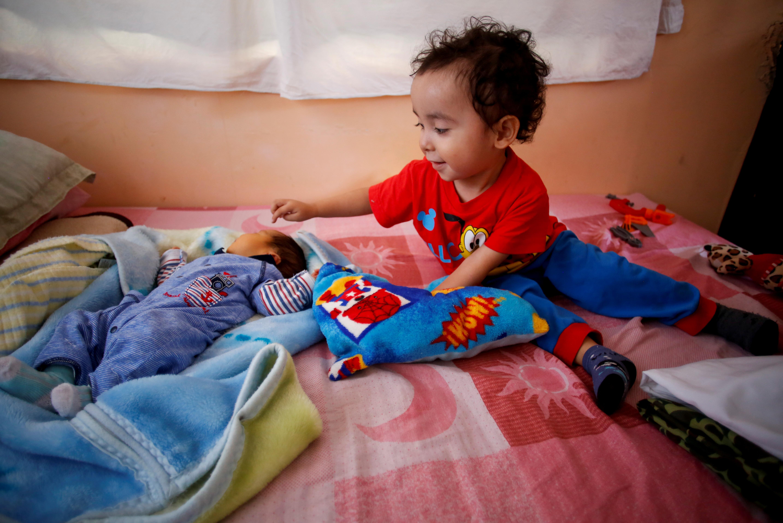 Angel Flores López, de 3 años, señala a su hermano recién nacido Sabino Yoehi Flores López mientras se sientan en una cama en el apartamento de sus abuelos, en Iztapalapa, Ciudad de México, México, 4 de junio de 2020. Foto: REUTERS / Gustavo Graf.