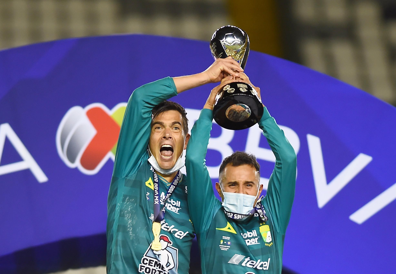Juan Gonzalez y Luis Montes celebran con el trofeo de la Liga MX.