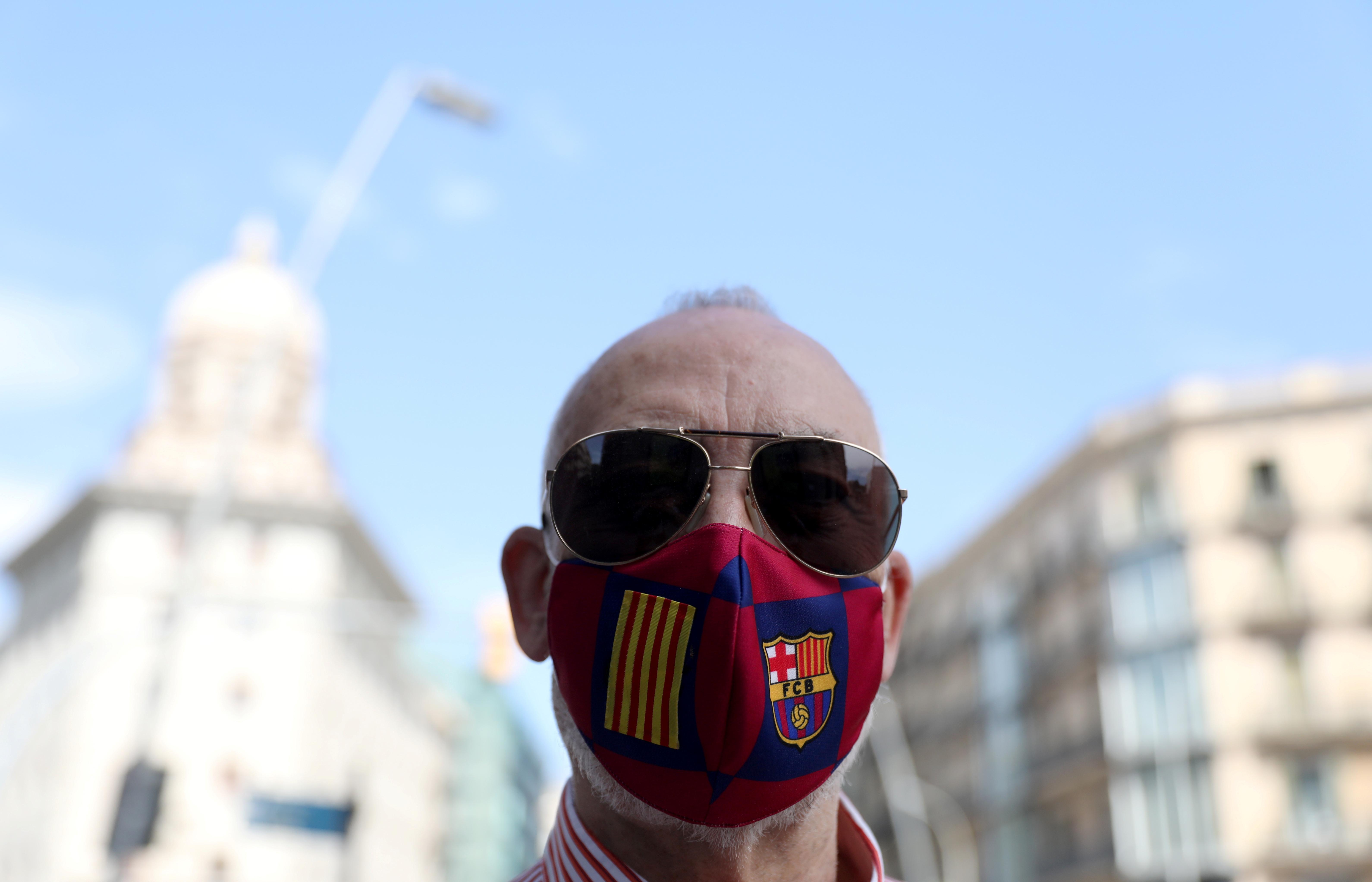 Un hombre con un barbijo del club de fútbol de Barcelona en Plaza Catalunya (REUTERS/Nacho Doce)