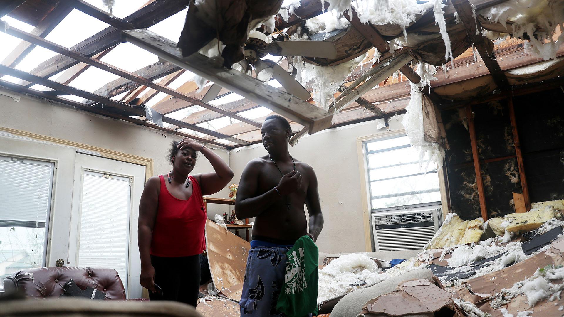 Latasha Myles y Howard Anderson están de pie en su sala de estar, donde estaban sentados cuando el techo se voló alrededor de las 2:30 am cuando el huracán Laura pasó por la zona en Lake Charles, Louisiana (Joe Raedle/Getty Images/AFP)