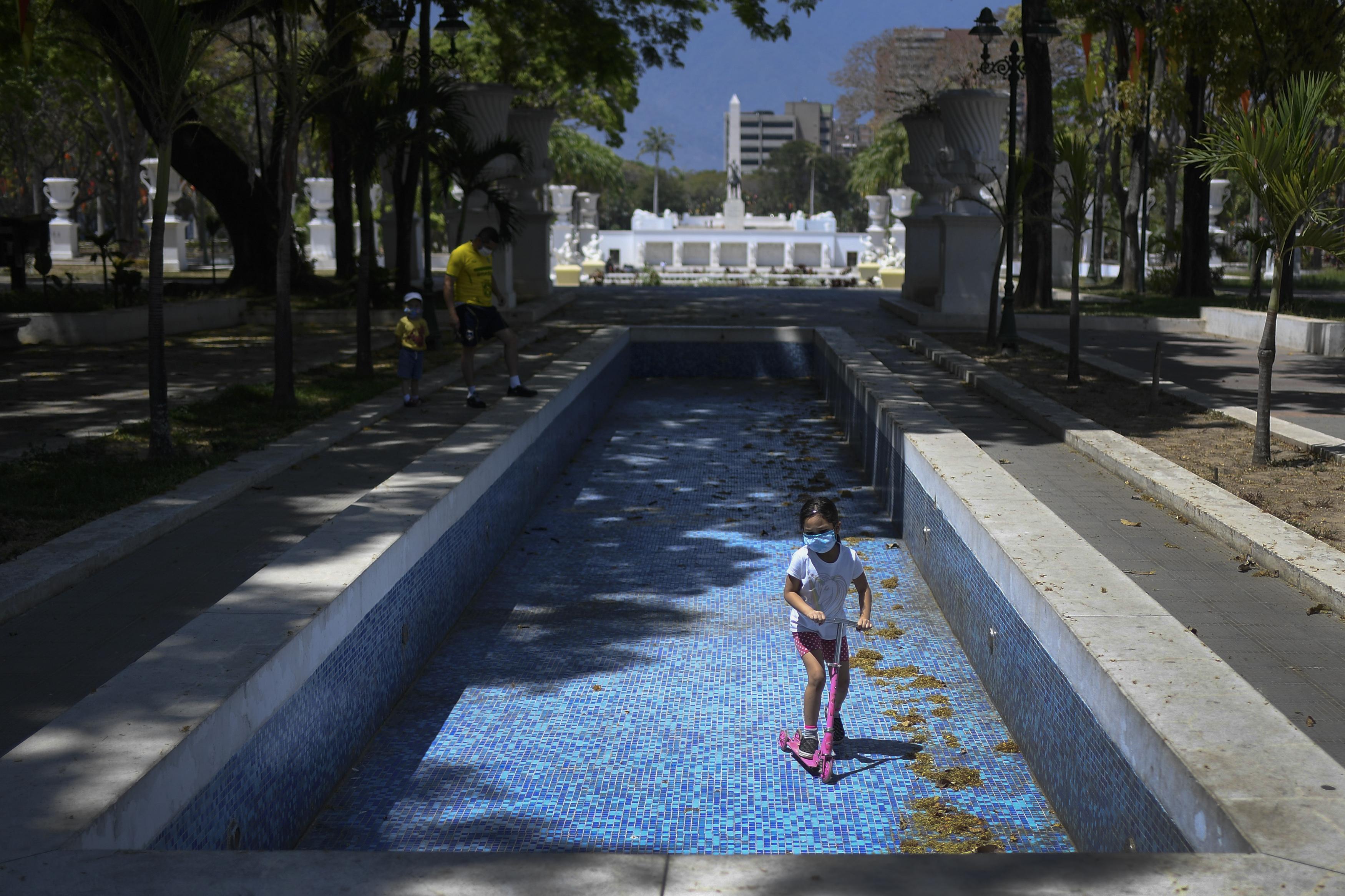 Una niña, con mascarilla para protegerse del coronavirus, juega con su patinete dentro de una fuente vacía en el paseo de Los Próceres, en Caracas, Venezuela, el 26 de abril de 2020. Se estima que el 86% de los venezolanos reportó problemas con el suministro de agua, incluyendo un 11% que no tiene, según una encuesta realizada por la ONG Observatorio Venezolano de Servicios Públicos entre 4.500 residentes en abril. (AP Foto/Matías Delacroix)