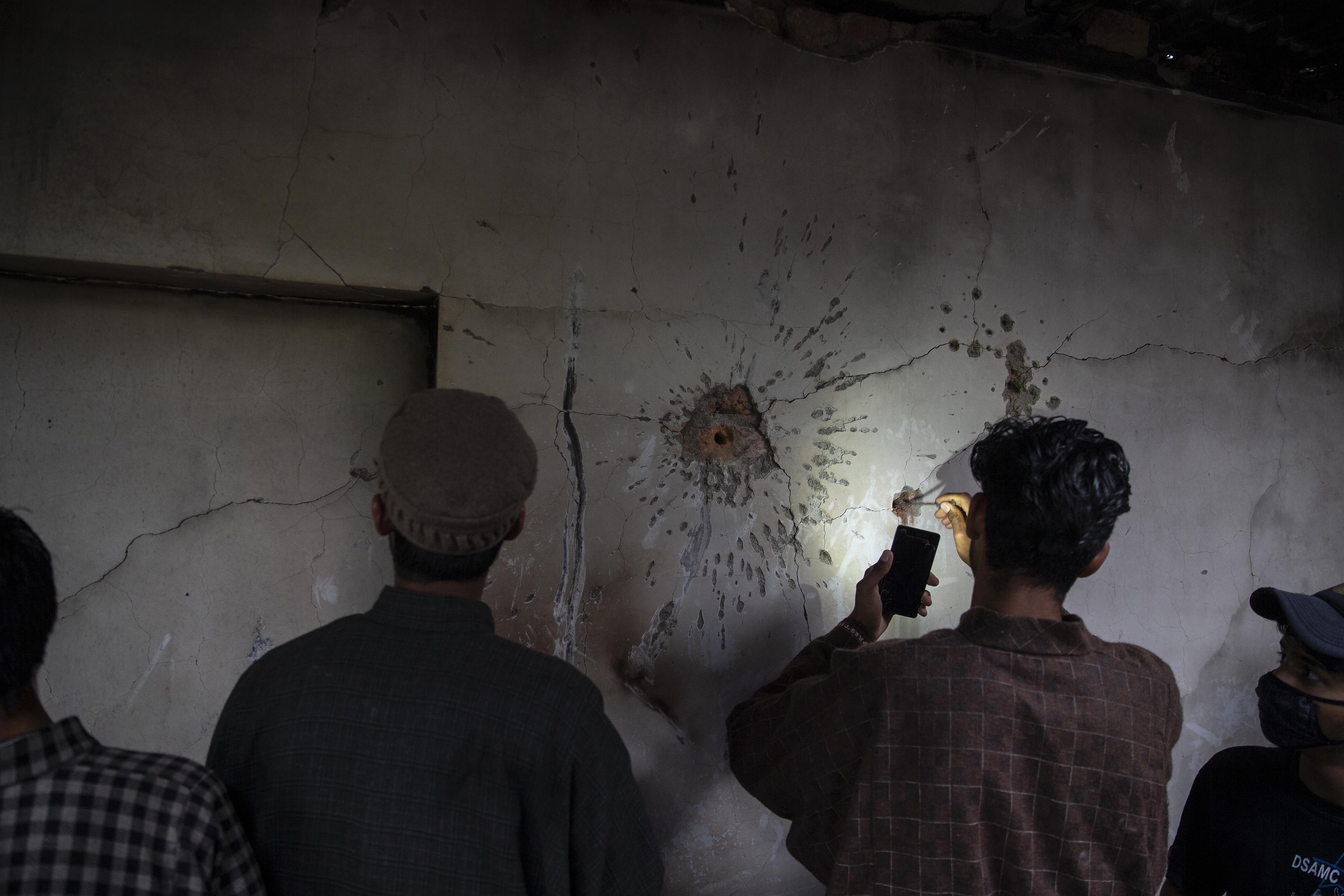 Un niño de Cachemira intenta sacar una bala de la pared de una casa dañada después de un tiroteo en Tral, al sur de Srinagar, Cachemira, el 24 de mayo de 2019. (Foto AP / Dar Yasin)