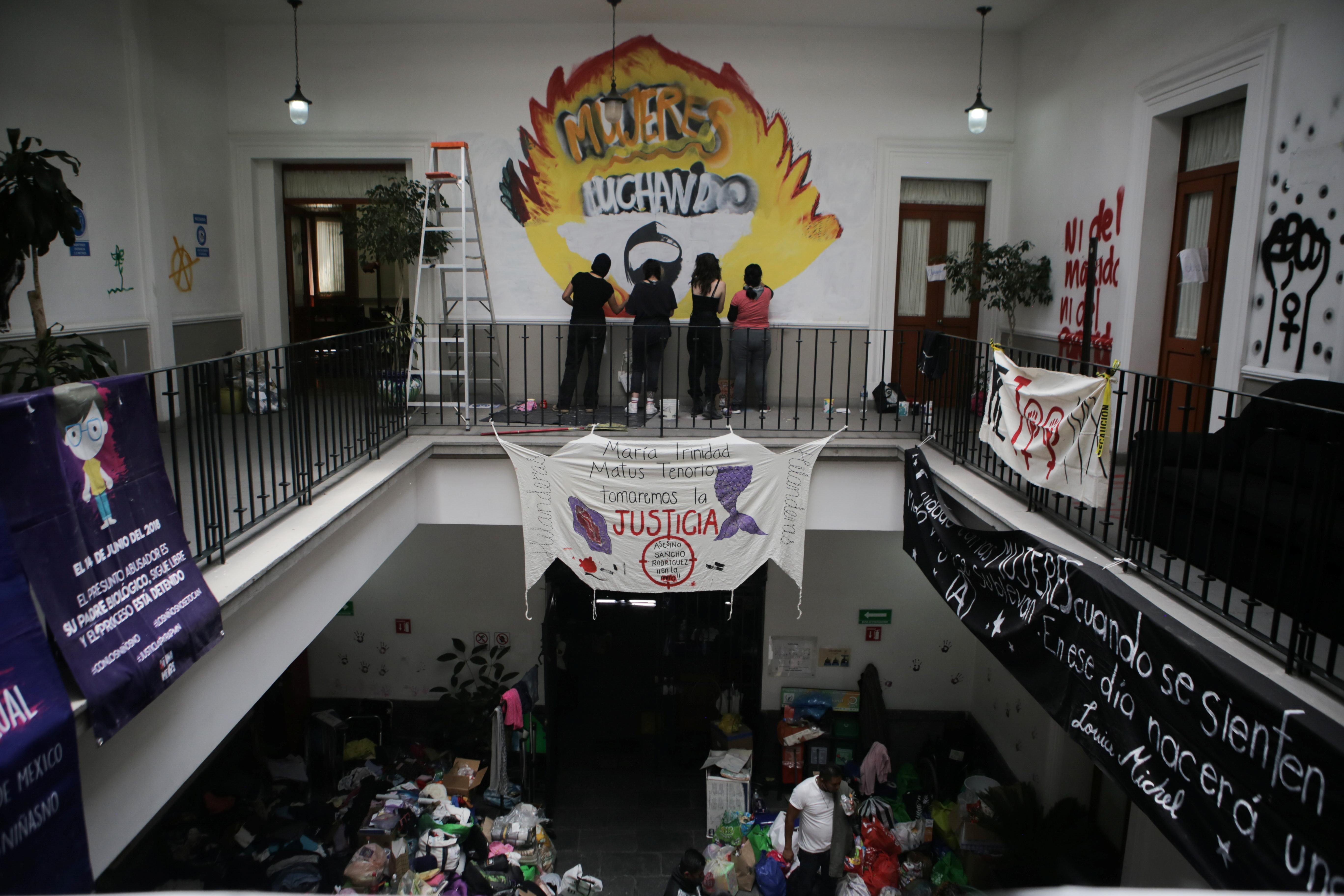 Miembro de un colectivo feminista pinta un graffiti dentro de las instalaciones del edificio de la Comisión Nacional de Derechos Humanos, en apoyo a víctimas de violencia de género, en la Ciudad de México, México, 10 de septiembre de 2020. Fotografía tomada el 10 de septiembre de 2020.