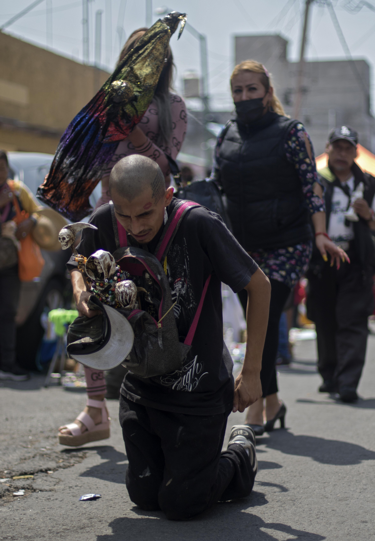Un hombre camina de rodillas portando figuras de Santa Muerte frente a su santuario en la calle Alfarería, en el barrio Tepito, de la Ciudad de México, el 1 de octubre de 2020