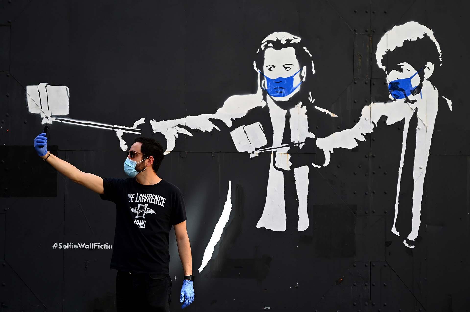Un hombre se toma una selfie junto a un stencil de los actores Samuel L. Jackson y John Travolta en la películas