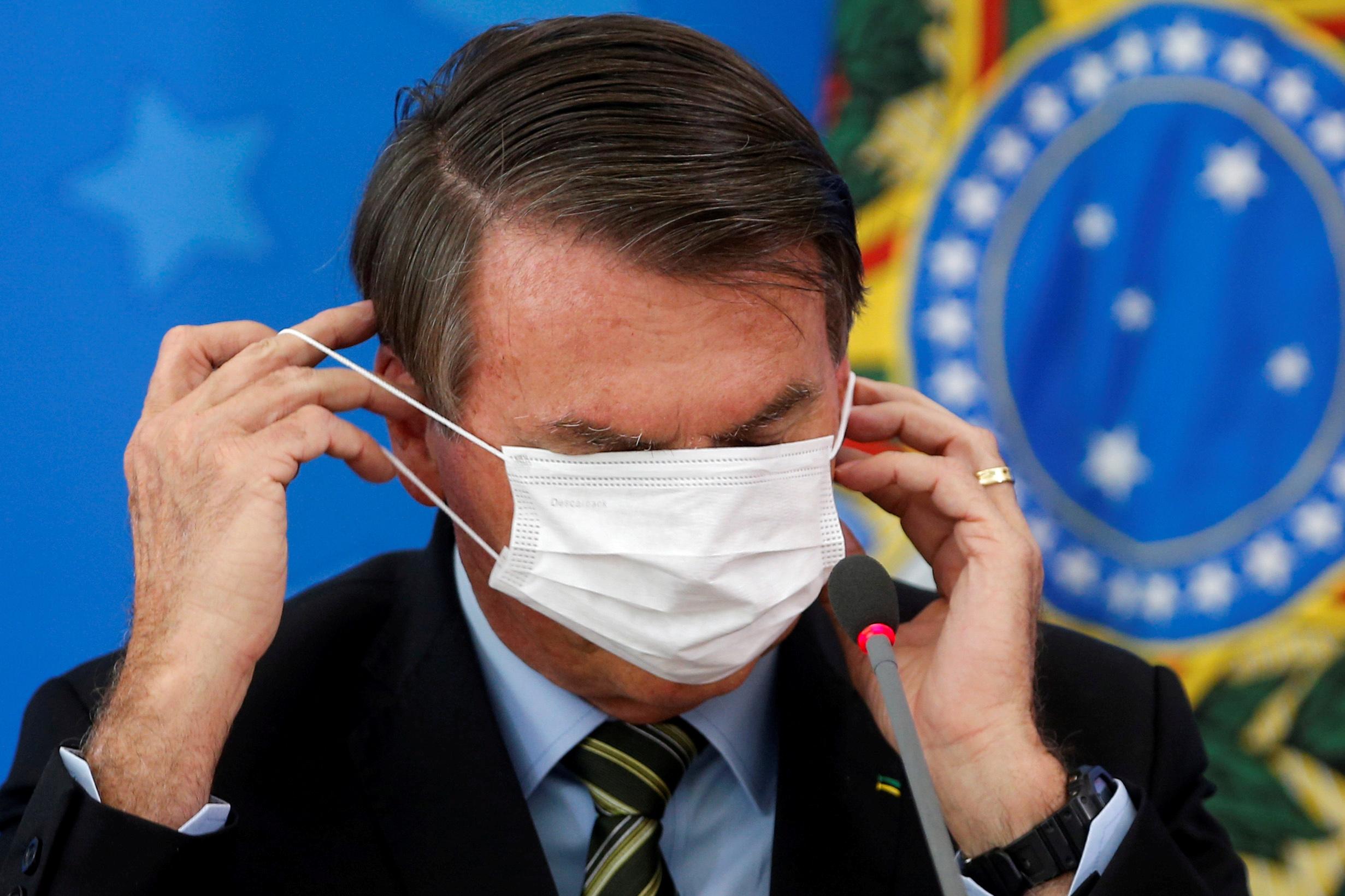El 18 de marzo, con cierto fastidio, el presidente Jair Bolsonaro se ajusta su máscara facial durante una conferencia de prensa en la que se anunciaron las primeras medidas contra la pandemia del coronavirus en Brasil (REUTERS/Adriano Machado)