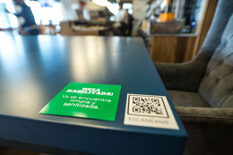 El cartel tiene dos caras: la verde indica que la mesa fue desinfectada y se puede usar. Del otro lado es roja y señala que aún no se puede ocupar. El código QR tiene la carta. Adiós a las de papel.