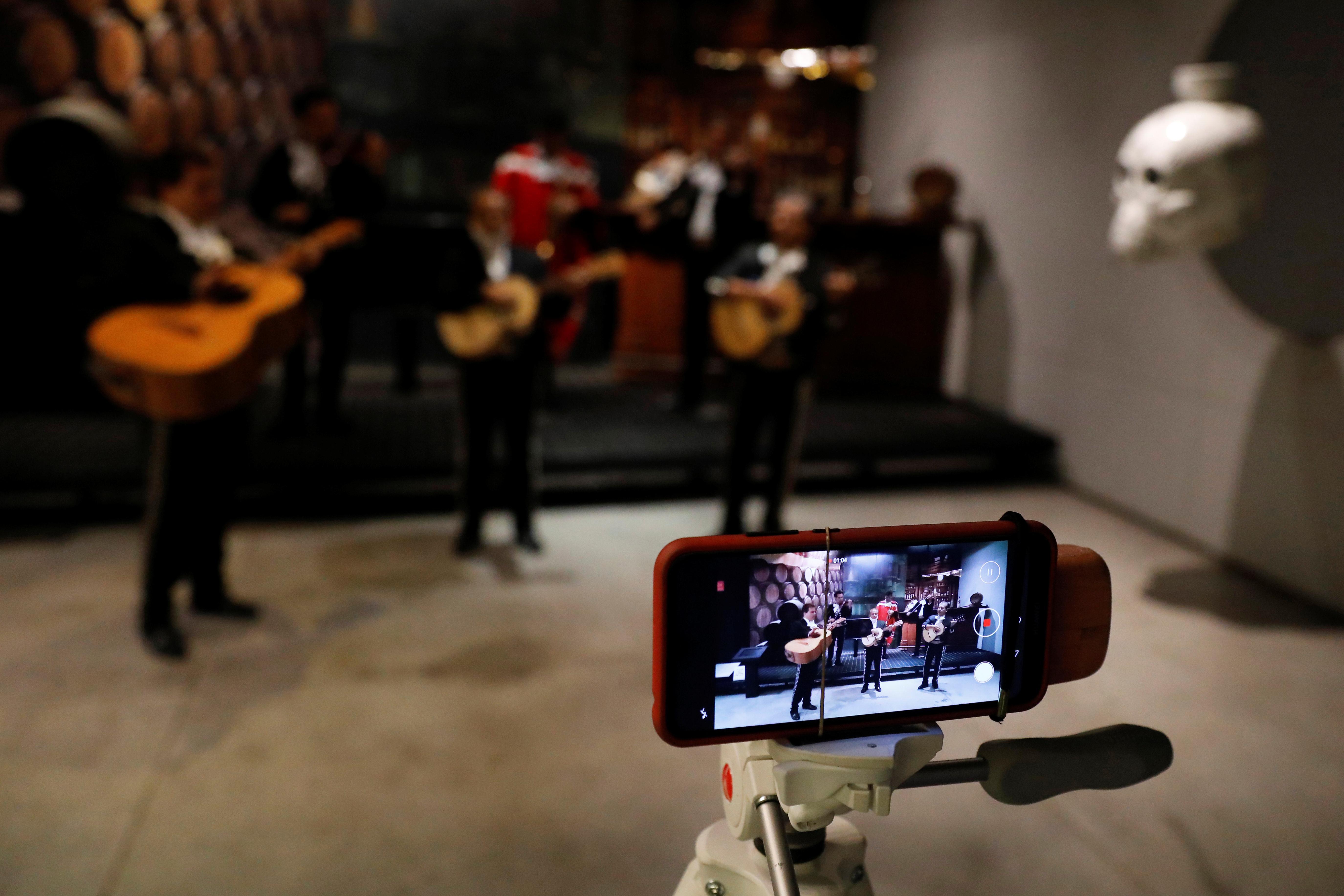 Un teléfono móvil graba un grupo de mariachis, mientras se presentan y reproducen música que se mostrará en línea para el Día de la Madre en la Ciudad de México, México. Mayo 9, 2020. (Foto: REUTERS/Carlos Jasso)