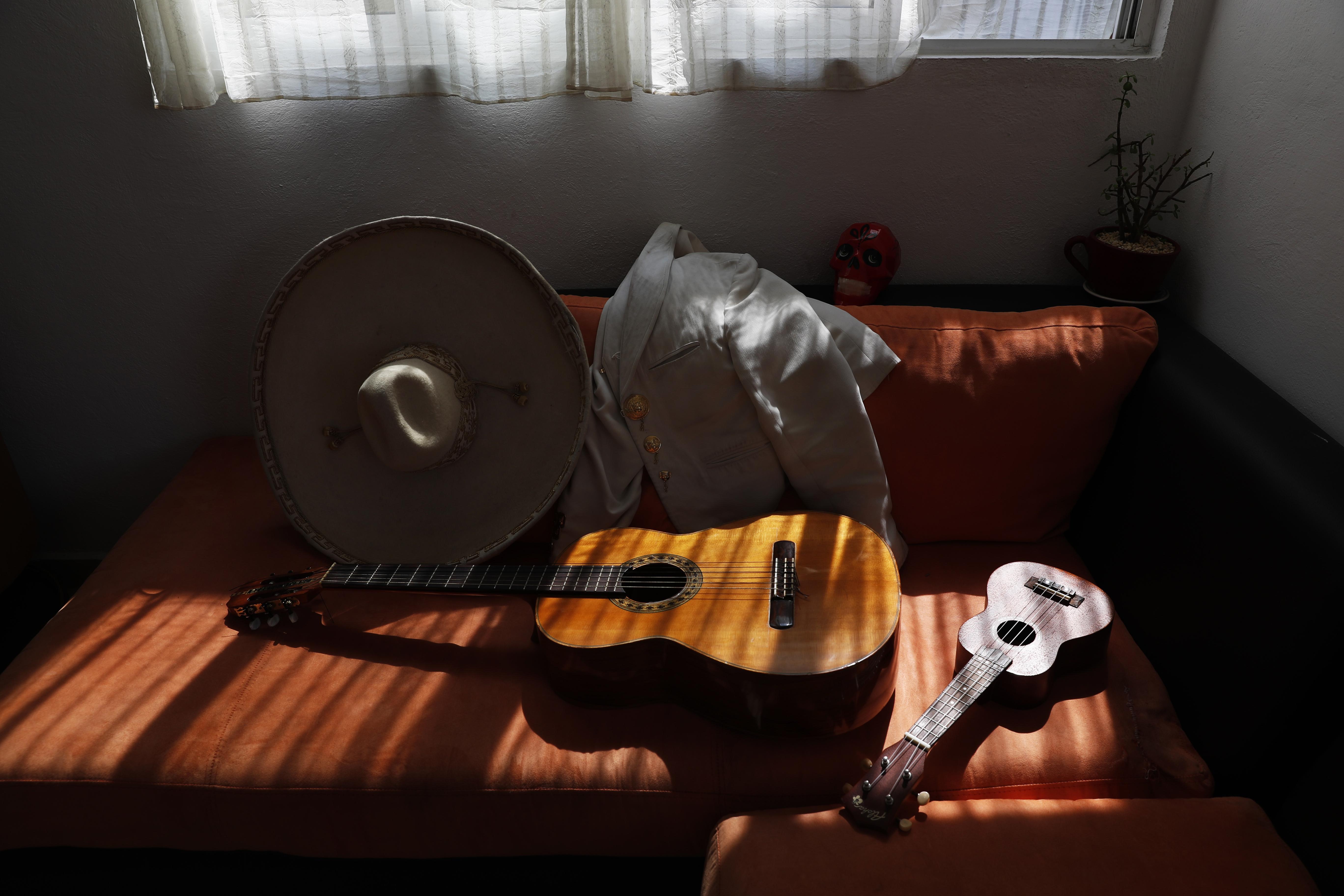 Los instrumentos musicales del Mariachi Duo Villa Maria, Sergio Carpio y Melissa Villar, reposan en el sofá mientras se preparan para tocar desde su casa durante el día de las madres en la Ciudad de México, el domingo 10 de mayo de 2020. El dúo está tocando Mariachi serenatas de forma remota como una forma de evitar el colapso de sus medios de vida causado por el nuevo bloqueo de la pandemia de coronavirus. Cada serenata a través del zoom dura unos 45 minutos. (Foto: AP/Marco Ugarte)
