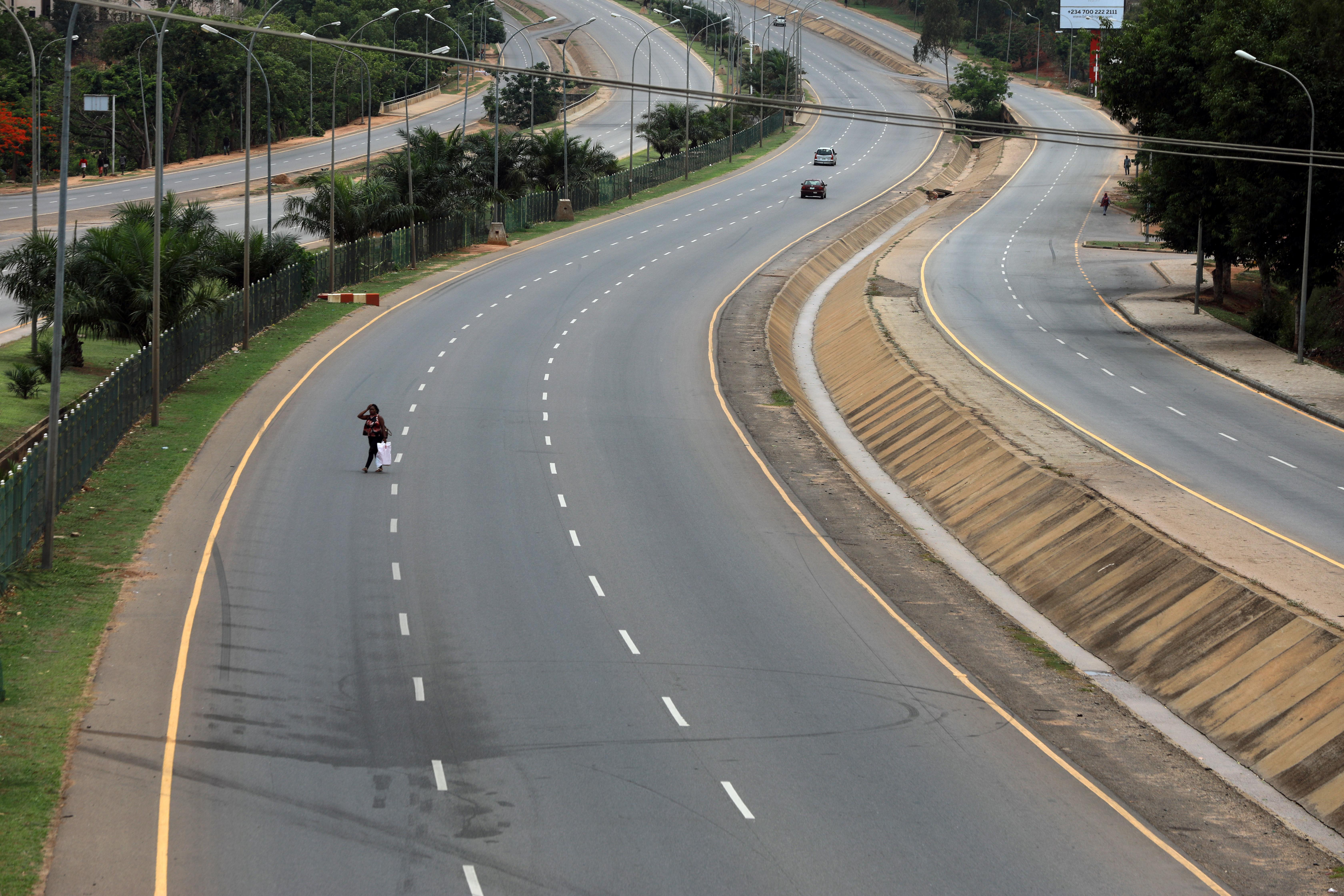 AHORA - Una mujer cruza una calle desierta en Abuja, Nigeria (REUTERS/Afolabi Sotunde)
