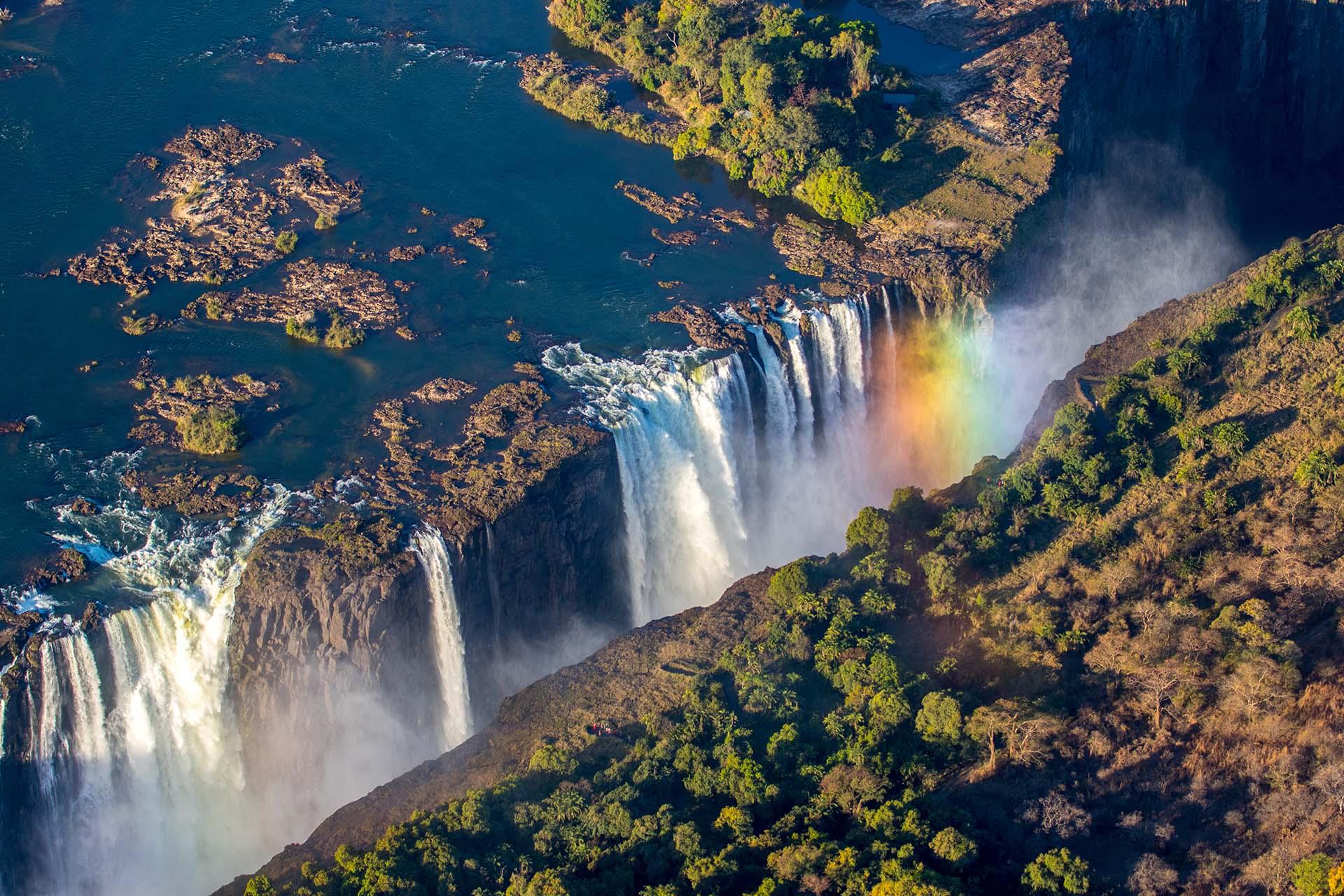 """Si bien no es la más alta, tiene el récord de la cascada más grande por volumen. En el siglo XIX, la tribu Kololo que vivía en el área apodó a las cataratas """"Mosi-oa-Tunya"""", que se traduce como """"El humo que truena"""""""