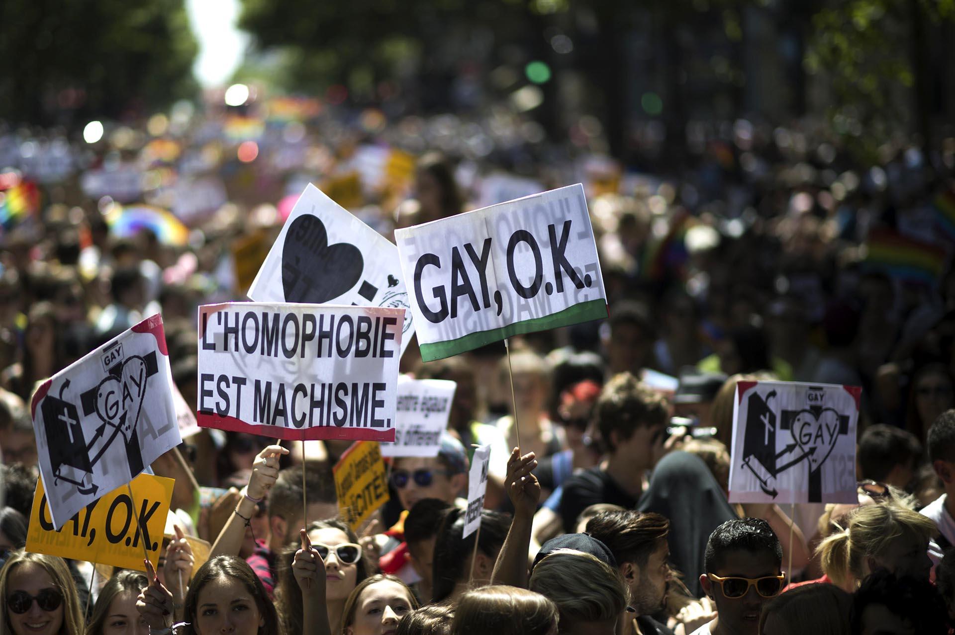 Manifestantes en París sostienen carteles que dicen