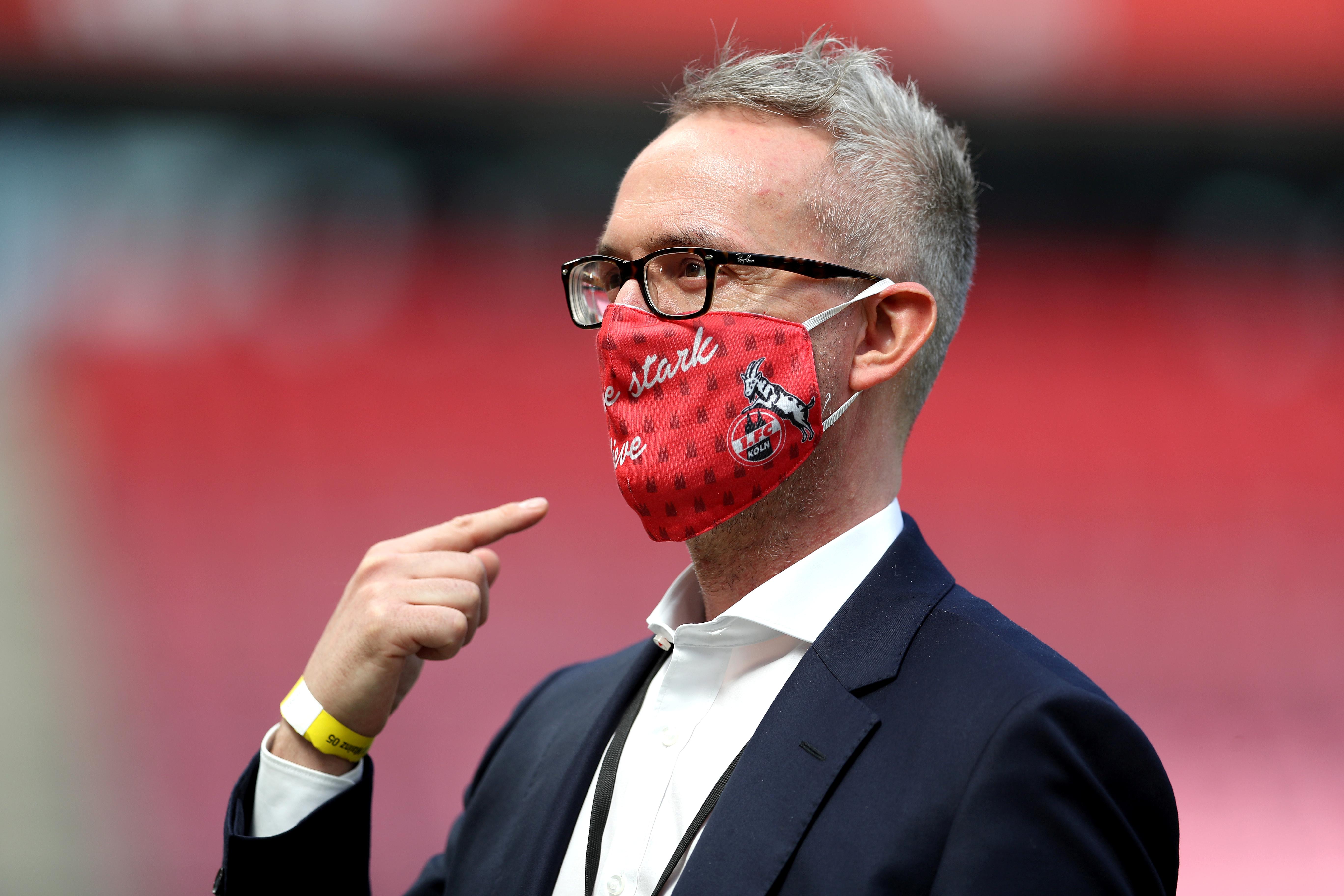 El entrenador del FC Colonia señala su barbijo con los colores y el escudo del club