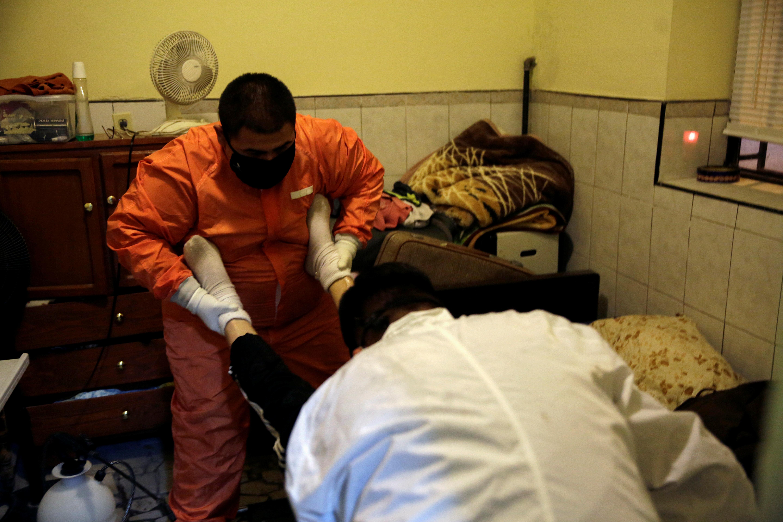 Empleados de la funeraria Ríos cargan el cuerpo de un hombre, que falleció por coronavirus (COVID-19), para trasladarlo a una funeraria en Ciudad Juárez, México, el 23 de octubre de 2020.
