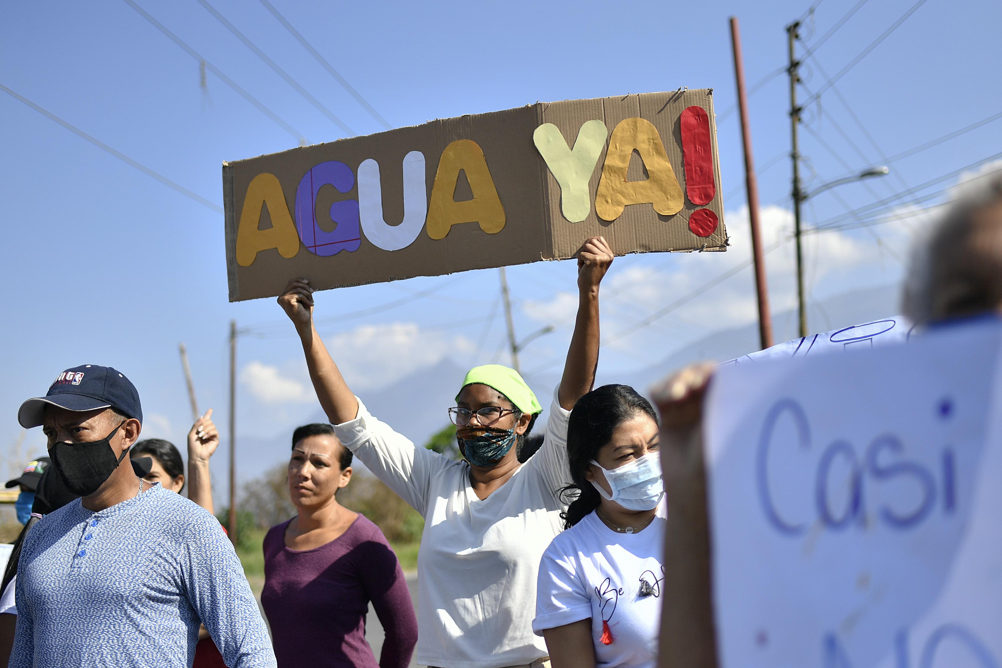 Residentes en el vecindario La Lira protestan por la falta de servicios públicos, incluyendo agua, en Caracas, Venezuela, el 21 de mayo de 2020. Se estima que el 86% de los venezolanos reportó problemas con el suministro de agua, incluyendo un 11% que no tiene, según una encuesta realizada por la ONG Observatorio Venezolano de Servicios Públicos entre 4.500 residentes en abril. (AP Foto/Matias Delacroix)