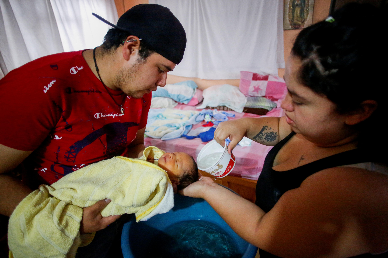 Miguel Flores Torres sostiene a su hijo recién nacido Sabino Yoehi Flores López con su esposa Karla López Rangel, quien lo dio a luz en su casa durante el brote de la enfermedad por coronavirus (COVID-19), lo baña en la casa de los padres de Rangel, donde se están quedando, en Iztapalapa, Ciudad de México, México, 31 de mayo de 2020. Foto: REUTERS / Gustavo Graf.