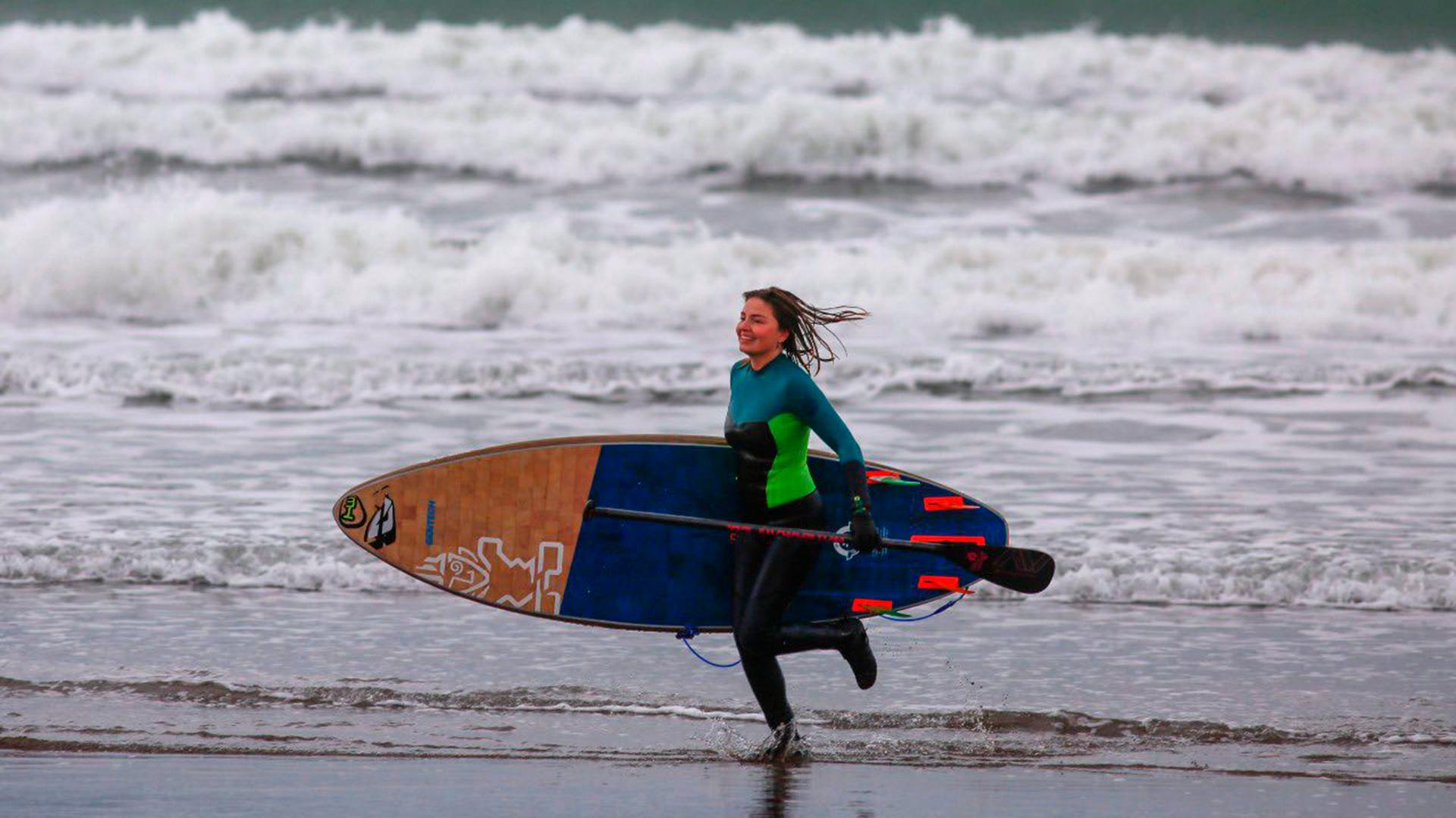 Una chica sale del agua con su equipo de padel surf. El mar se abrió para los que desafiaron las bajas temperaturas (@munimardelplata)