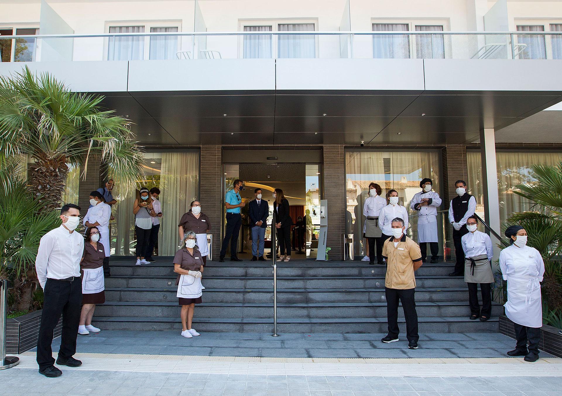 Empleados del hotel RIU Concordia de Palma de Mallorca dan la bienvenida a los turistas que comenzaron a llegar este lunes.