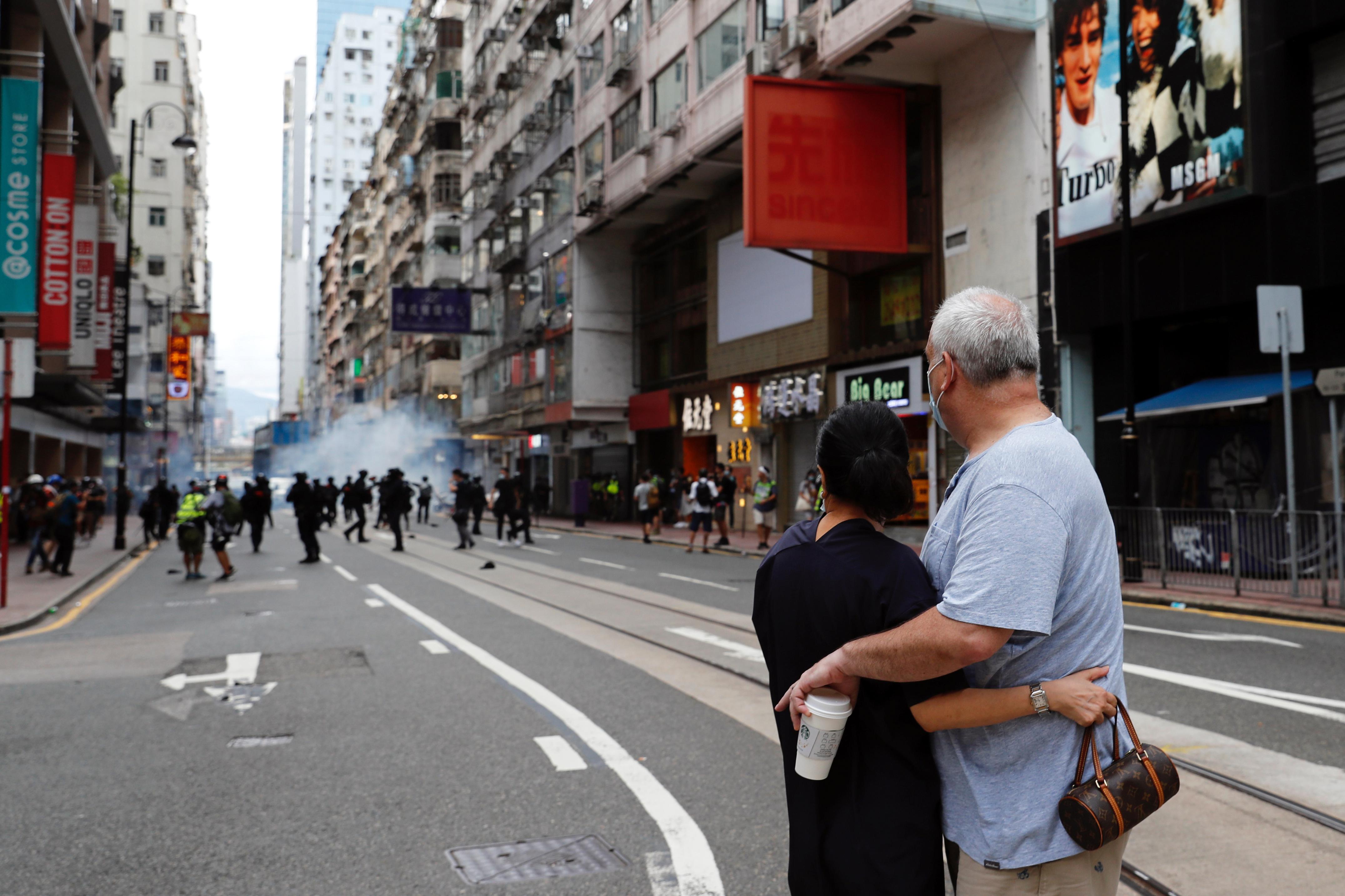 Una pareja se abraza mientras la policía dispara gases lacrimógenos