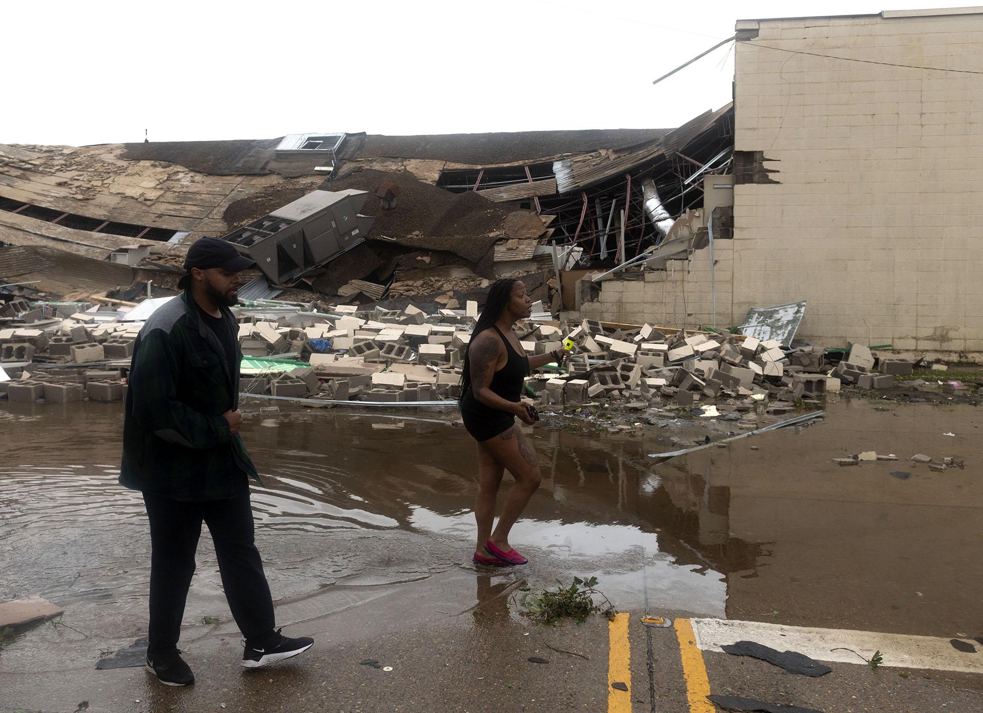 La gente pasa por delante de un edificio destruido tras el paso del huracán Laura en Lake Charles (Foto de ANDREW CABALLERO-REYNOLDS / AFP)