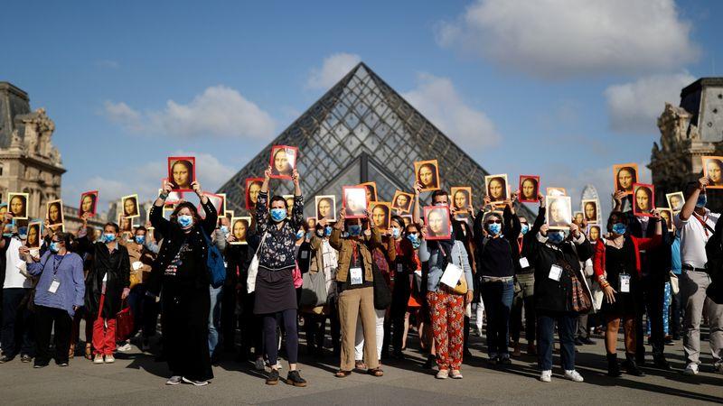 Guías turísticos de París sostienen retratos de la Mona Lisa, pintada por el artista Leonardo da Vinci, durante una manifestación en el patio del Museo del Louvre para advertir sobre sus condiciones de trabajo luego de que el museo reabrió sus puertas al público después de casi cuatro meses de cierre debido al COVID-19 (REUTERS/Christian Hartmann)