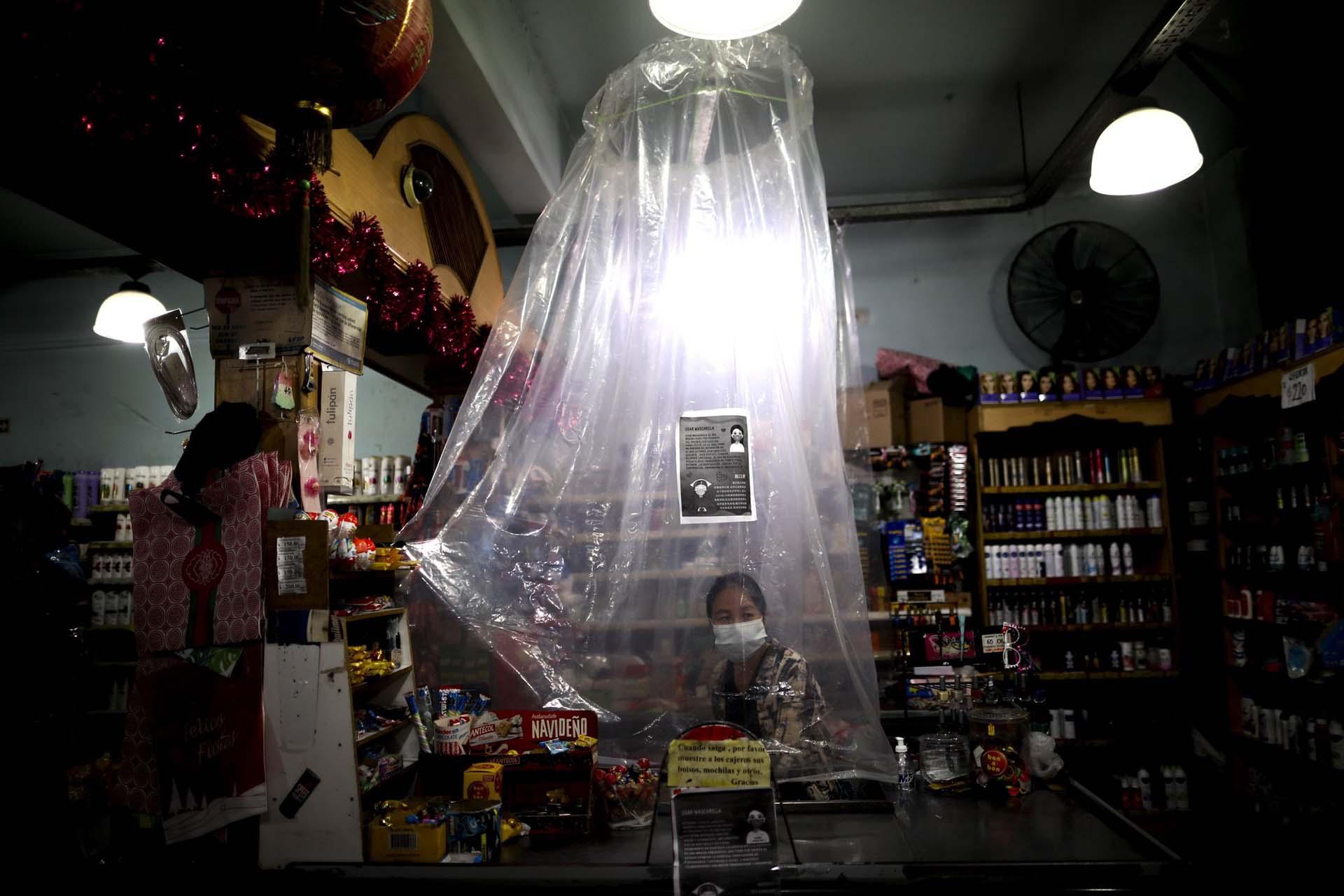 Allá por mediados de marzo, un cajero de un supermercado espera a los clientes detrás de una improvisada cortina de plástico como precaución contra el avance del coronavirus