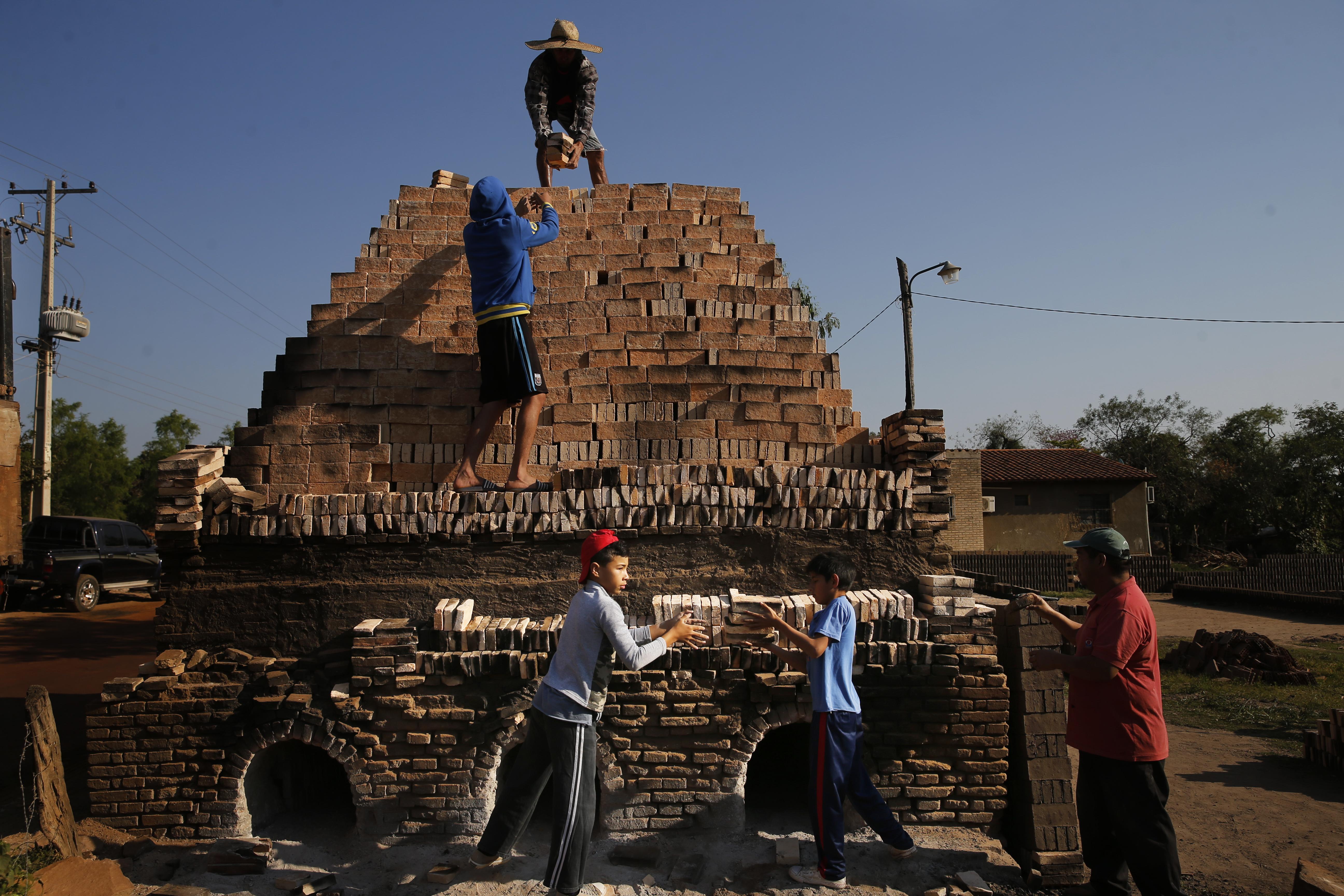 Los niños trabajan con sus familiares para cargar un horno con ladrillos de arcilla en Tobati, Paraguay, el viernes 4 de septiembre de 2020. En muchas de las pequeñas fábricas de ladrillos de Tobati, los lugareños comienzan a trabajar a una edad temprana para complementar los ingresos familiares.