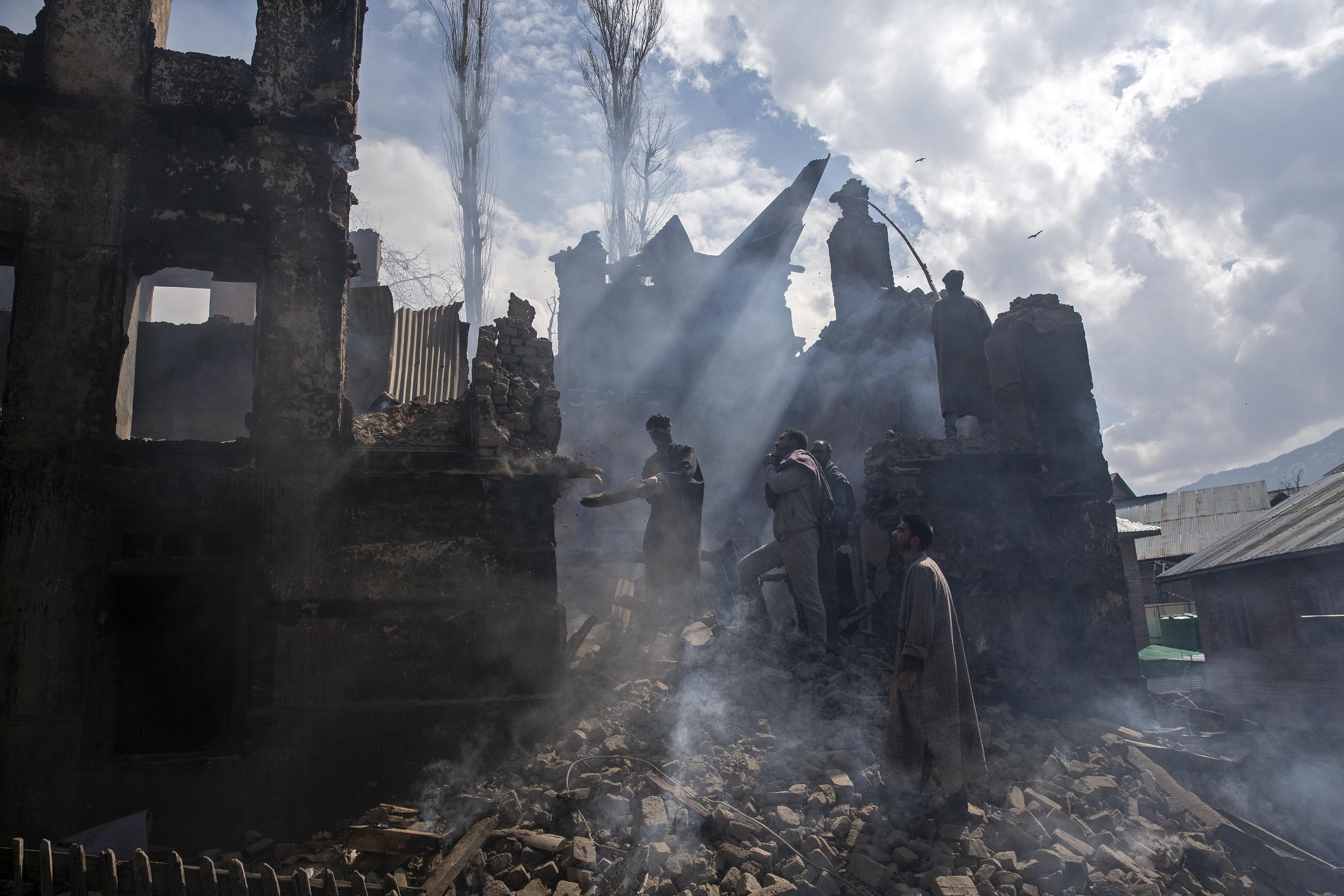 Los hombres de Cachemira desmantelan una parte de una casa destruida en un tiroteo en la aldea de Tral, al sur de Srinagar, Cachemira (Foto AP / Dar Yasin)