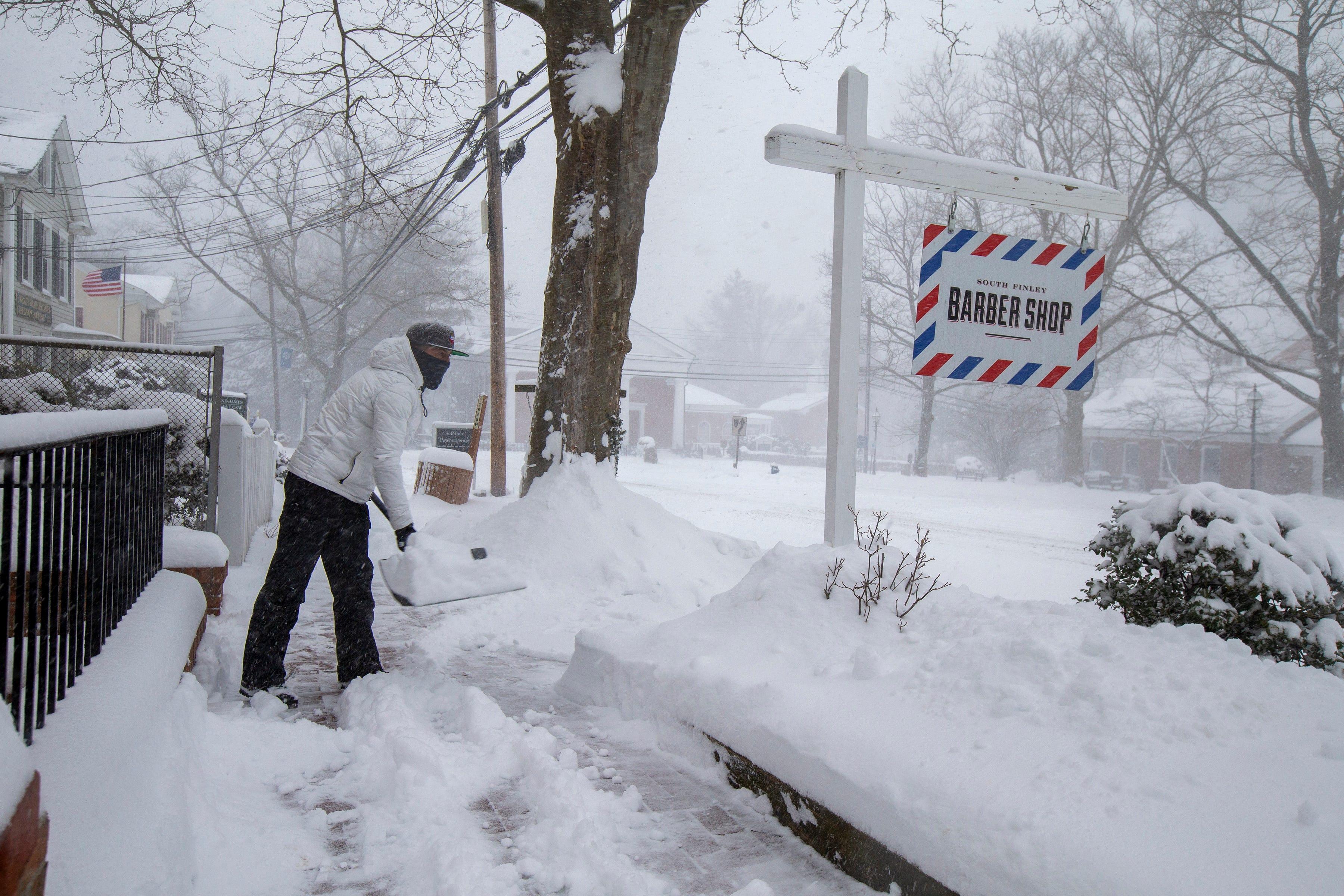 El barbero Bart Sienkiewicz quita la nieve frente a su tienda en Basking Ridge, Nueva Jersey (Tanya Breen/Courier News/USA TODAY NETWORK via REUTERS)