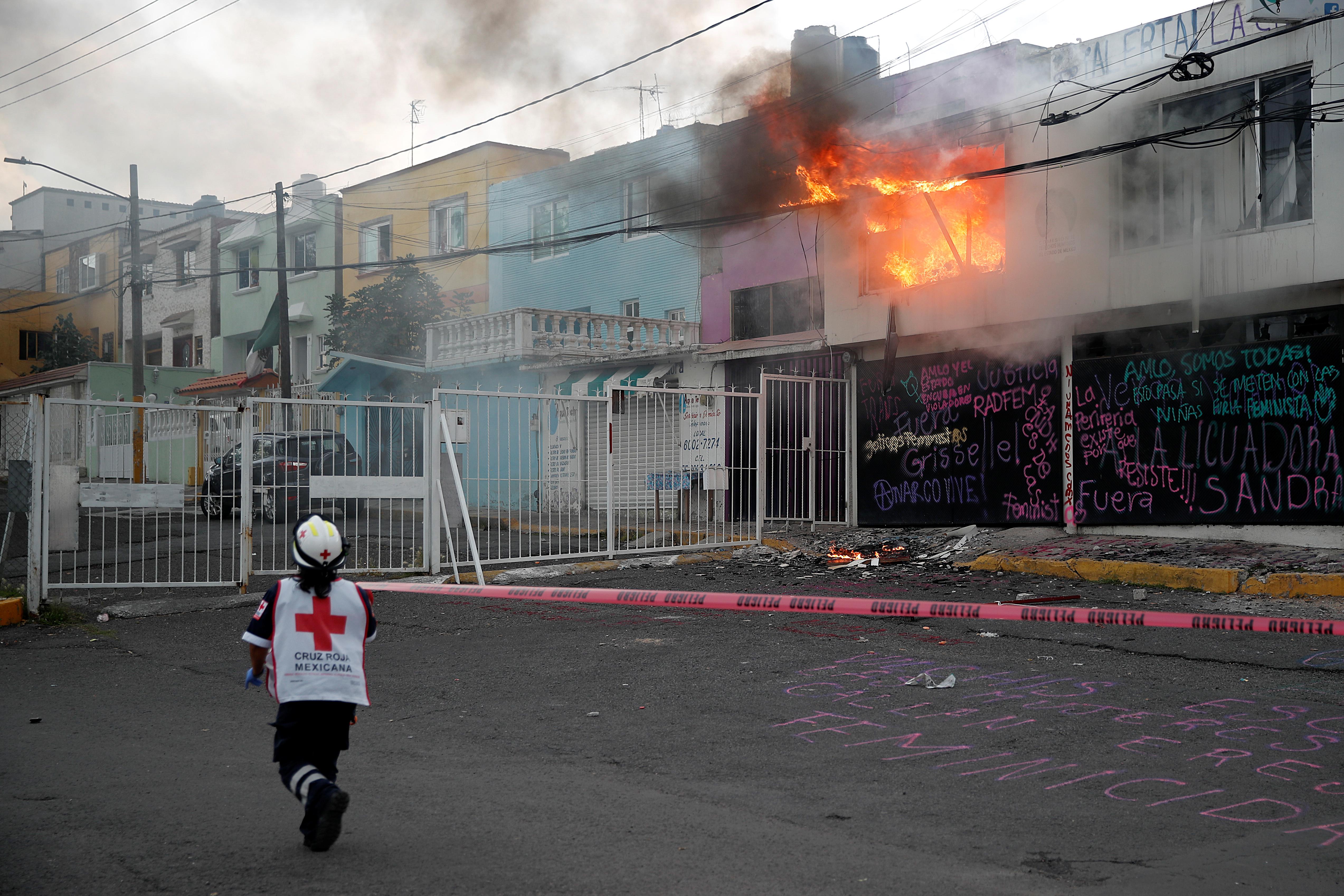 Un miembro de la Cruz Roja pasa junto a un incendio que estalló después de que miembros de un colectivo feminista vandalizaran las instalaciones de la comisión de derechos humanos del estado de México, en apoyo a las víctimas de violencia de género, en Ecatepec, Estado de México, México el 11 de septiembre de 2020.