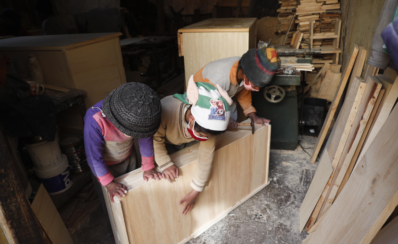 Tres de los niños Delgado, de derecha a izquierda, Yuri, 11, Wendi, 9 y Alison, 8, hacen un cajón en el taller de carpintería familiar en El Alto, Bolivia, el miércoles 2 de septiembre de 2020.