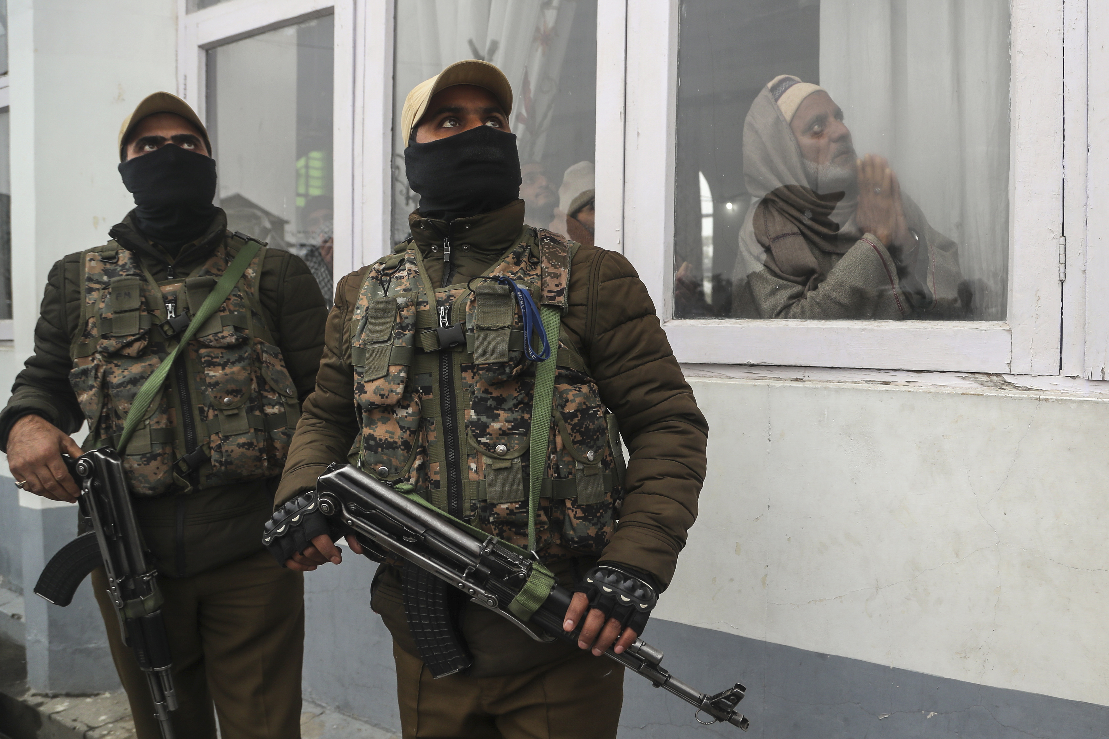 Policías indios vigilan mientras los musulmanes de Cachemira rezan y el sacerdote jefe, invisible, muestra una reliquia del profeta Mahoma del Islam en el santuario de Hazratbal, con motivo del aniversario del nacimiento del profeta en Srinagar, India, el 10 de noviembre de 2019. (AP /Mukhtar Khan)