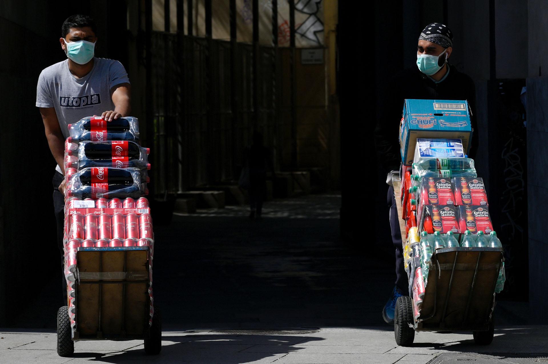 Dos proveedores de bebidas llevan su carga en una calle de Barcelona, España.