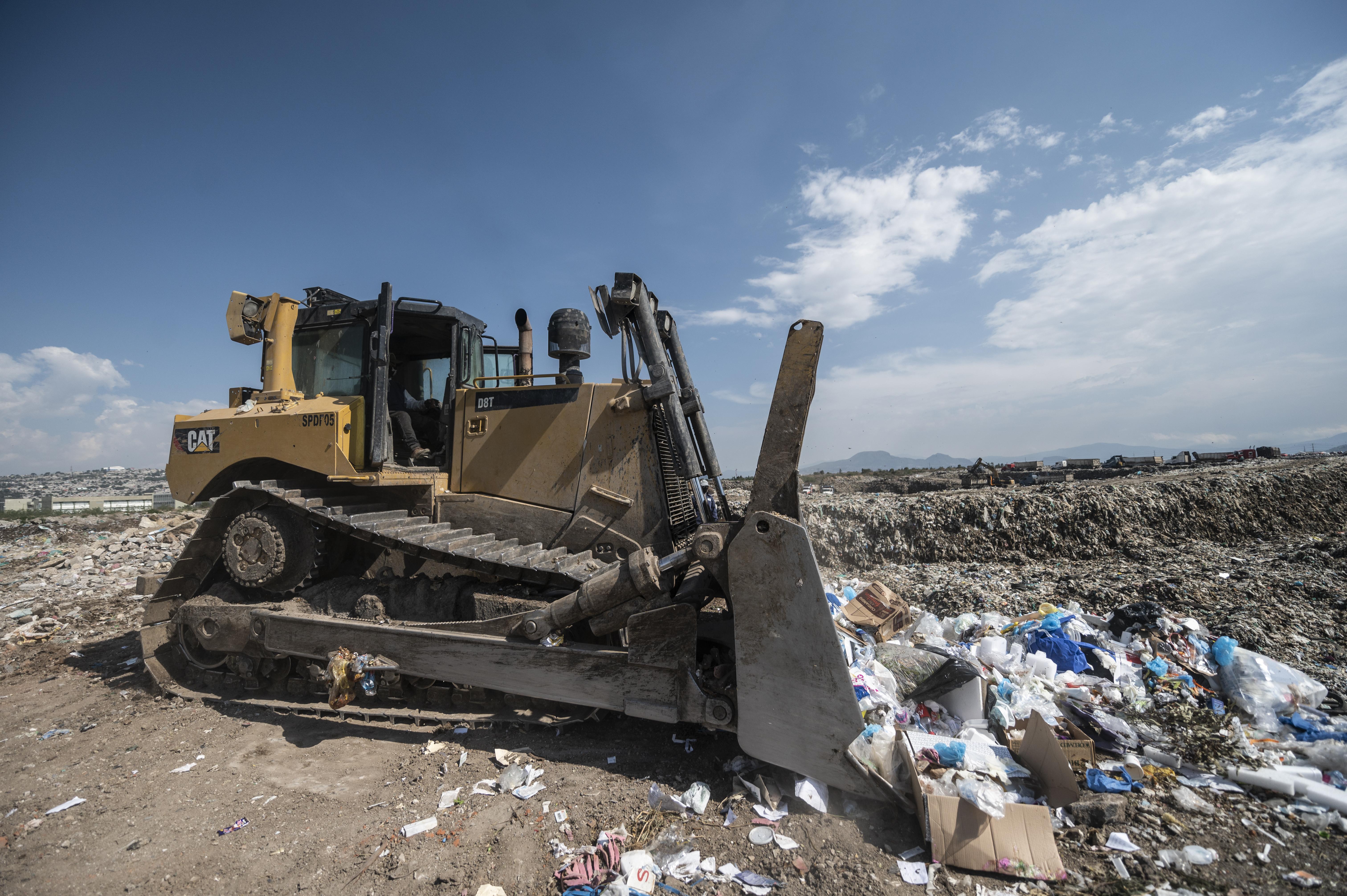 Una excavadora organiza los desechos médicos en el basurero