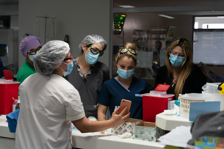 Juliana Torquati, Deborah Russo y dos enfermeras más miran una imagen del teléfono de su compañera. Todo lo que hablan mientras están ahí es relacionado a los pacientes.