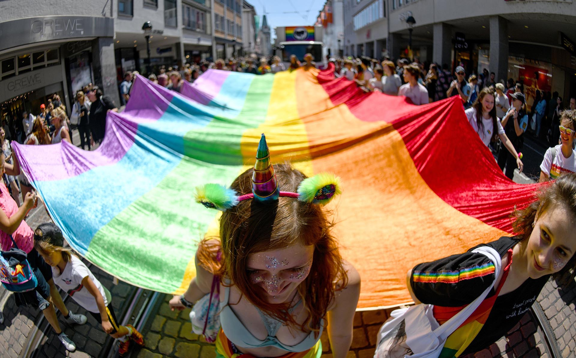 Los participantes del desfile del orgullo Christopher Street Day llevan una bandera con los colores del arco iris mientras caminan por las calles de Friburgo, en el sur de Alemania, el 23 de junio de 2018